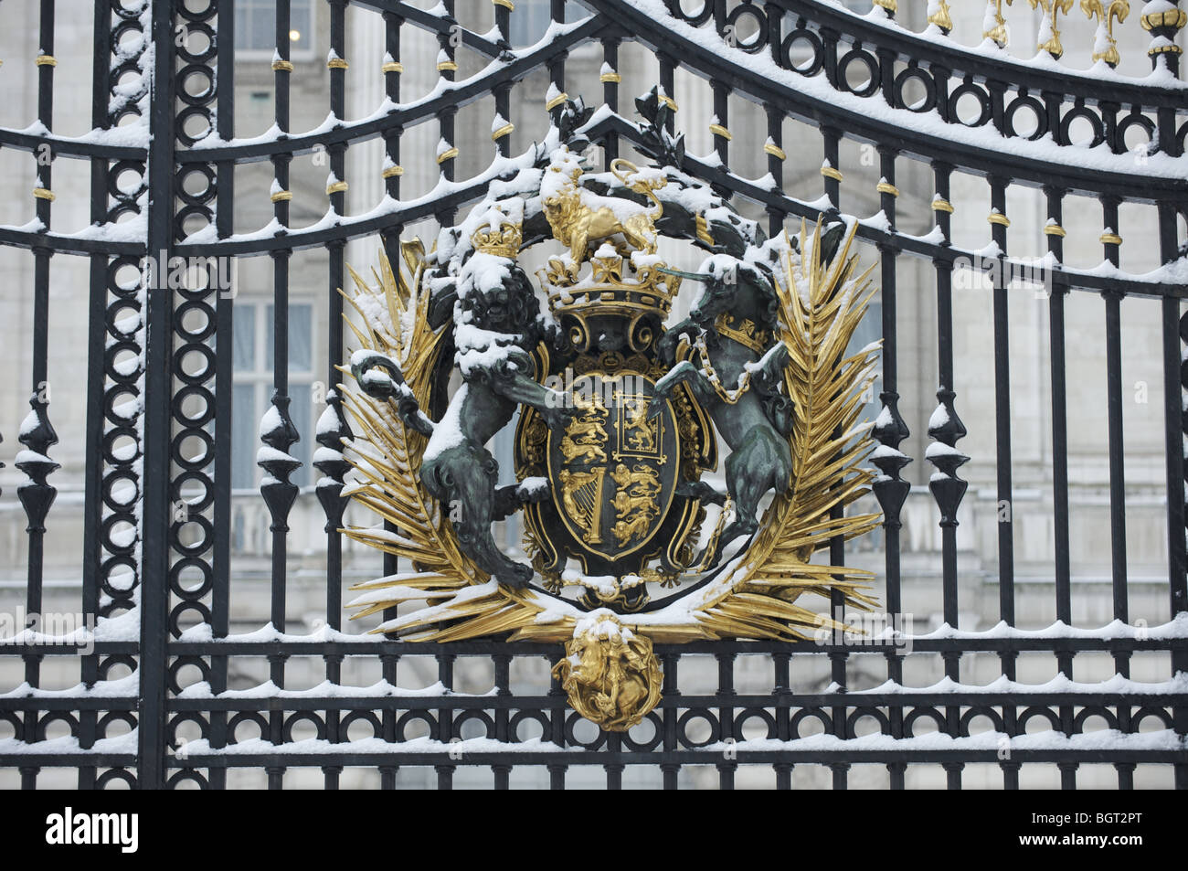 The royal coat of arms on Buckingham Palace gates in the snow - Stock Image