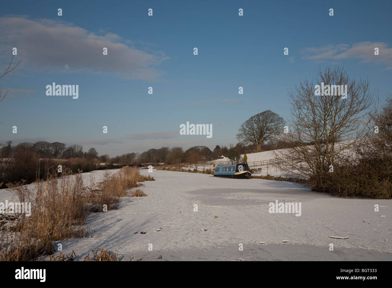 ice bound narrowboats narrow boats on a frozen Lancaster Canal in winter on a cold sunny day Stock Photo