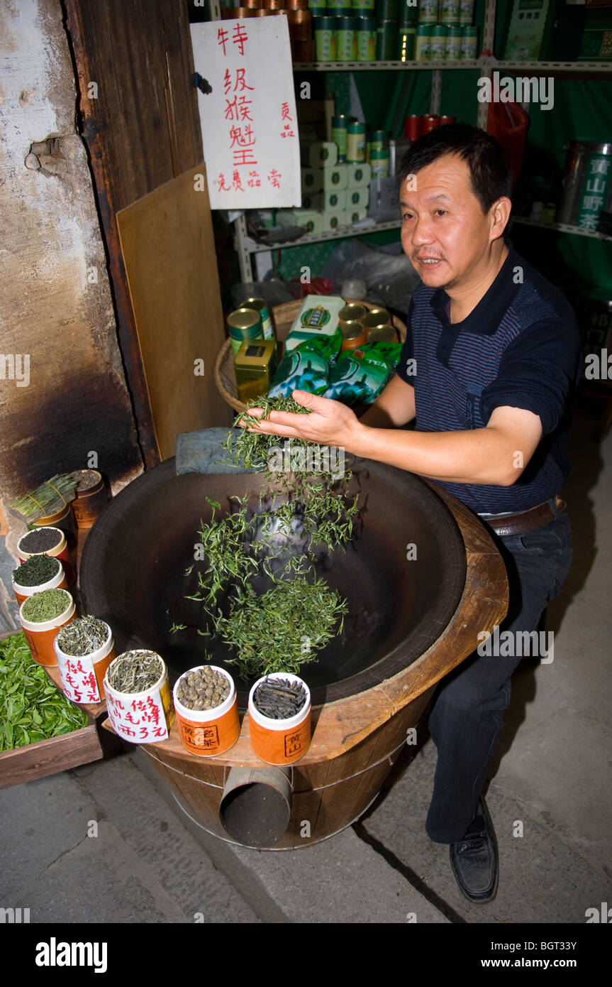 Man drying green tealeaves and selling it to tourists. Hongcun. Anhui province, China. - Stock Image