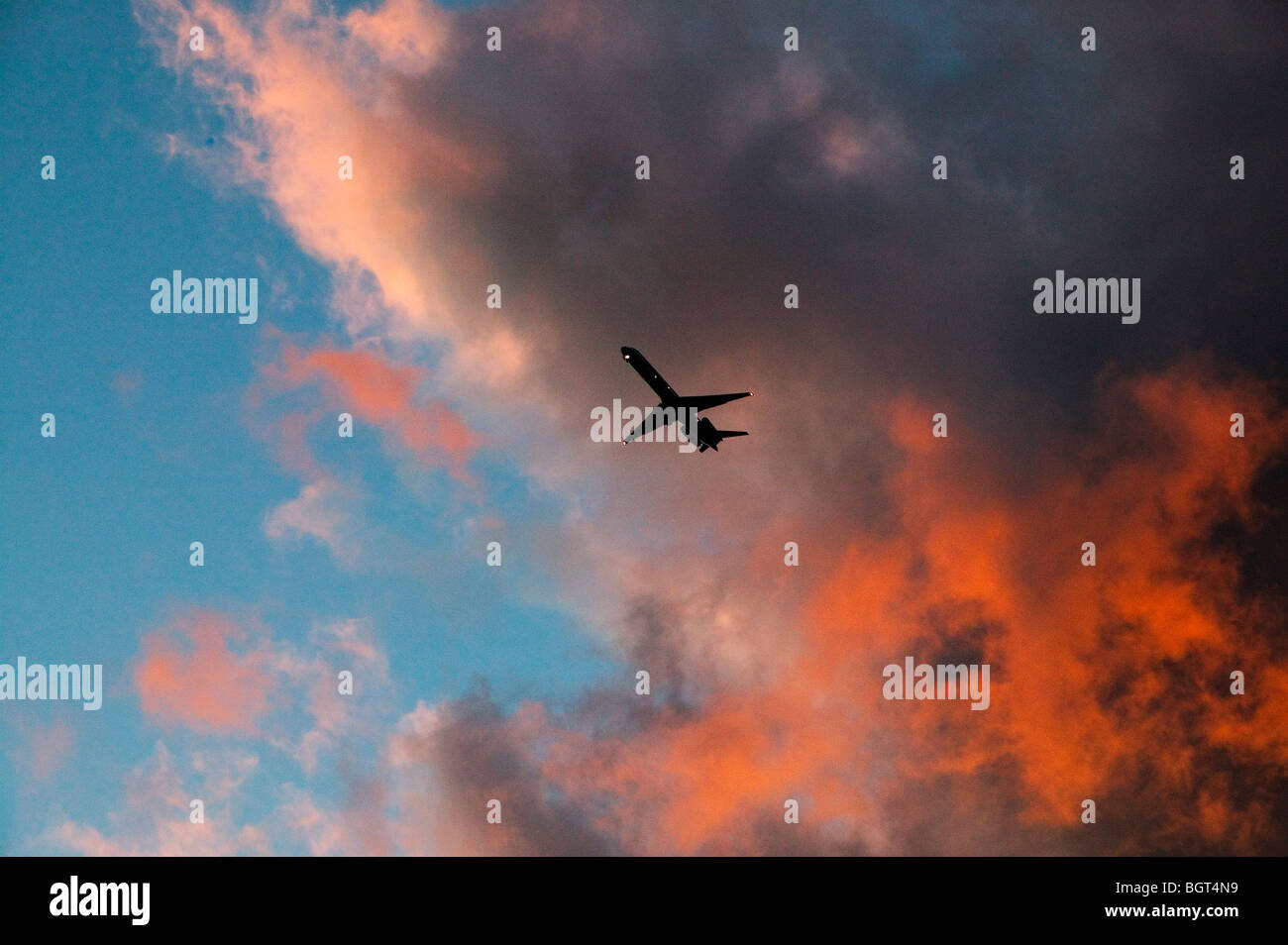 Jet on approach to land during sunset - Stock Image