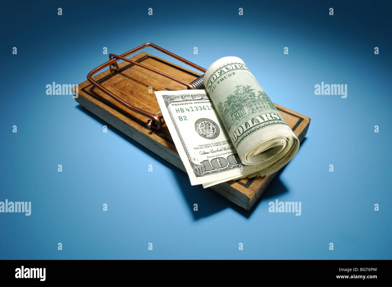A roll of money sitting on an armed wooden mousetrap Stock Photo