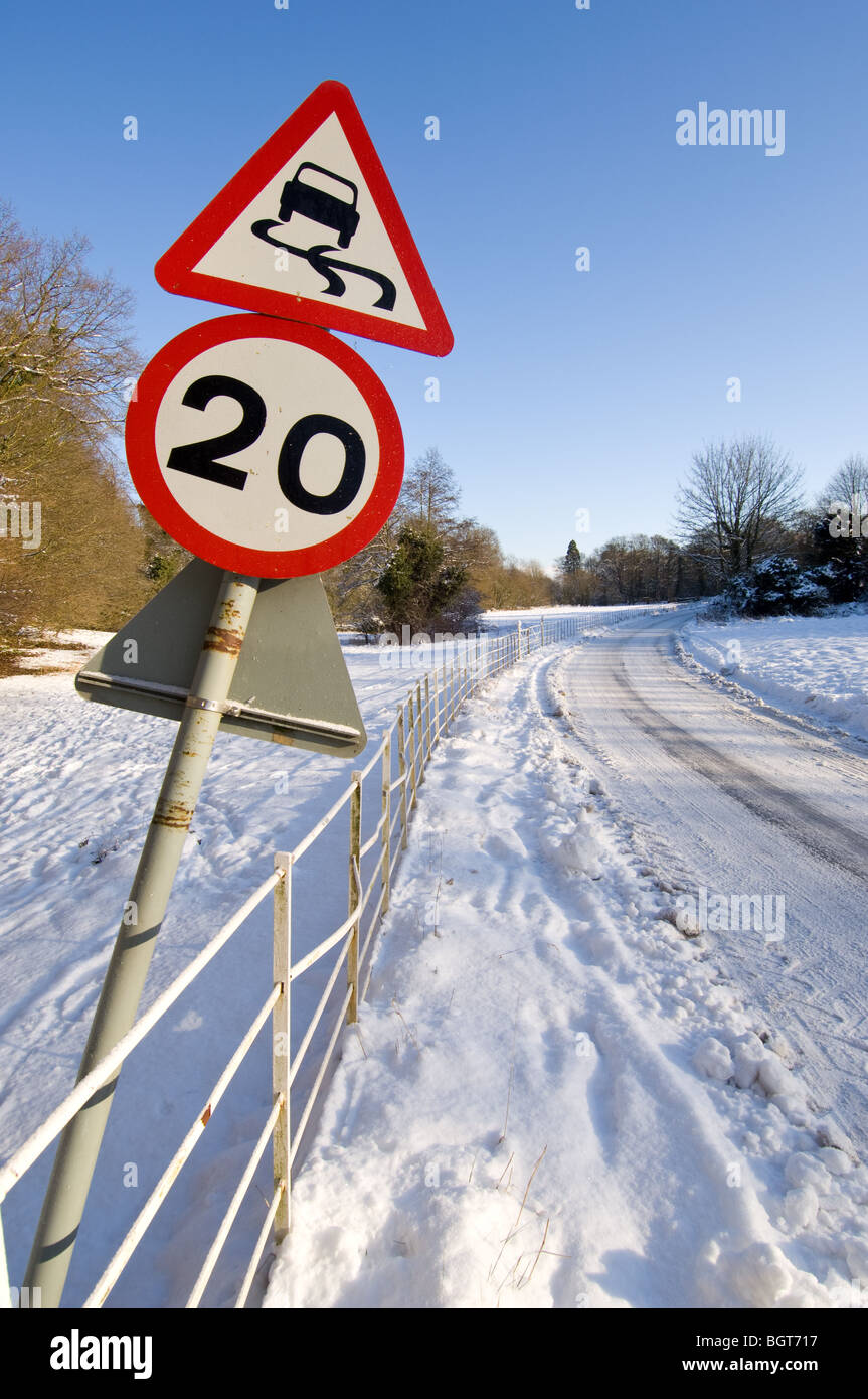 Warning signs, 20 m.p.h. and slippery road informing motorist of the hazard ahead during the winter snow fall. - Stock Image