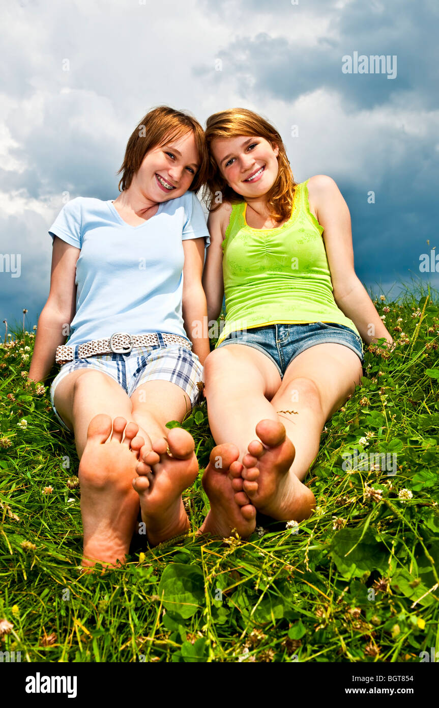 Two young teenage girl friends sitting barefoot on summer ...