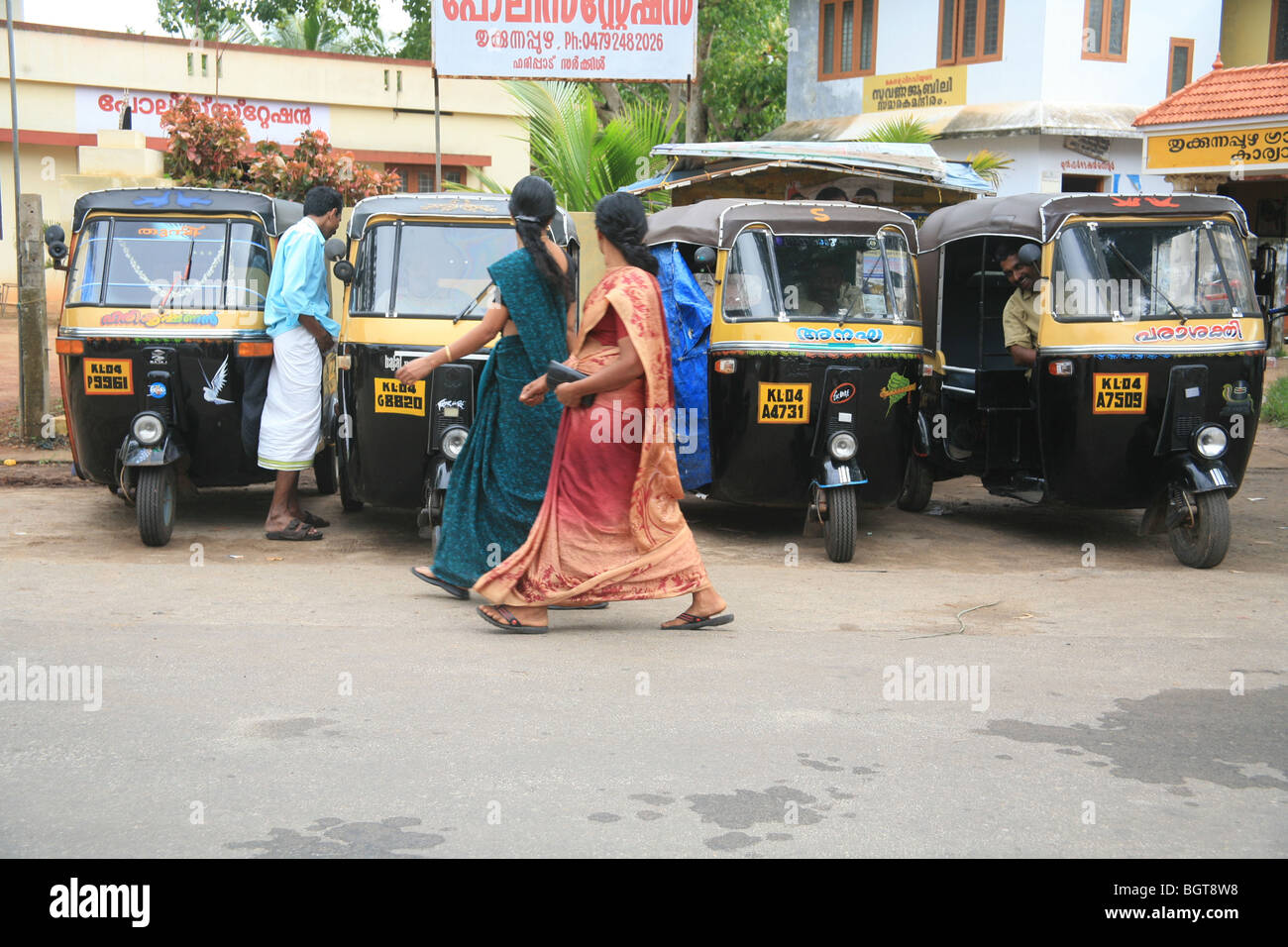 People walking past parked Tut Tuts, Kerala, India - Stock Image