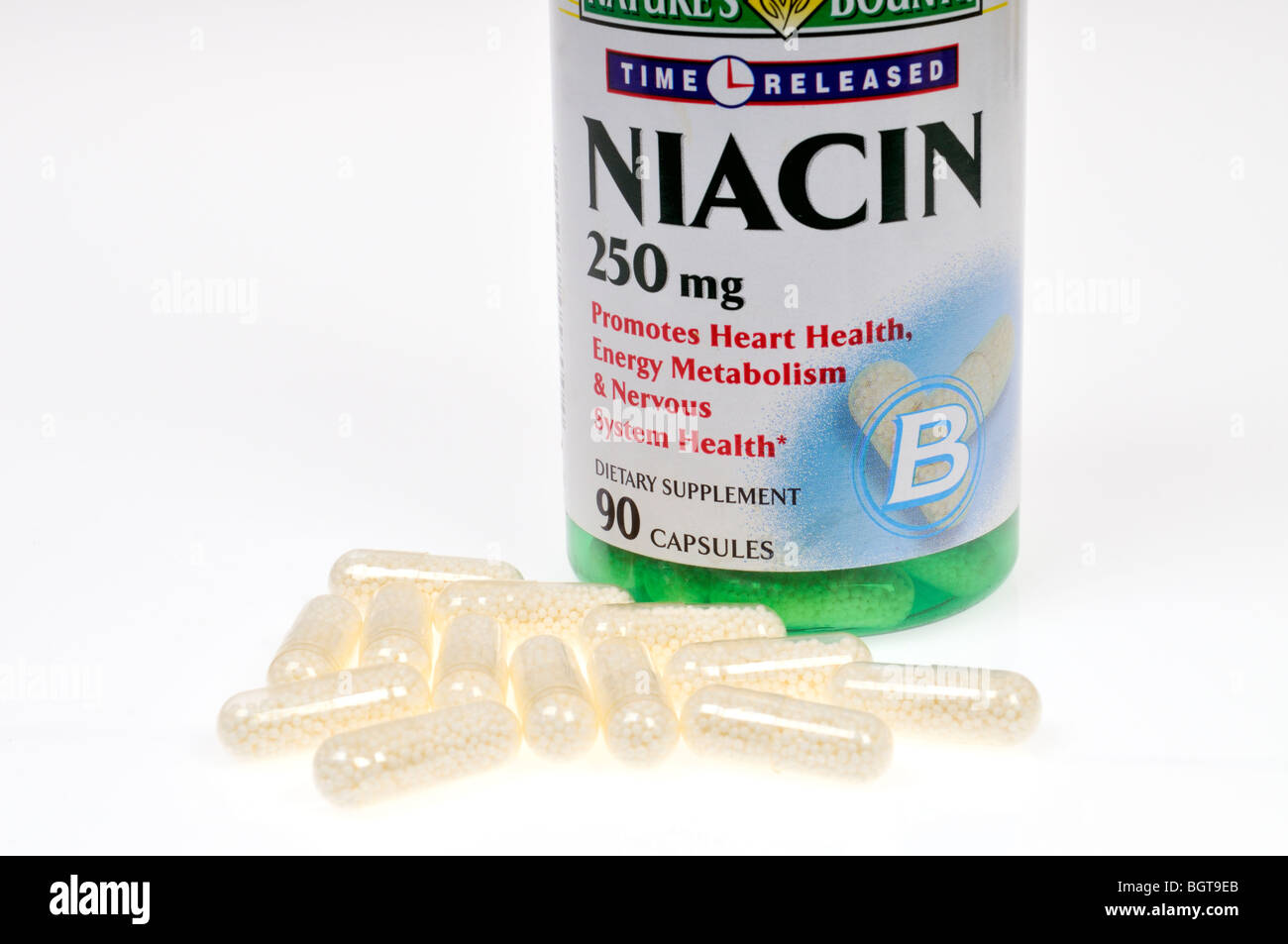 A bottle of Niacin dietary supplements with some capsules scattered out of bottle on white background, cutout. - Stock Image