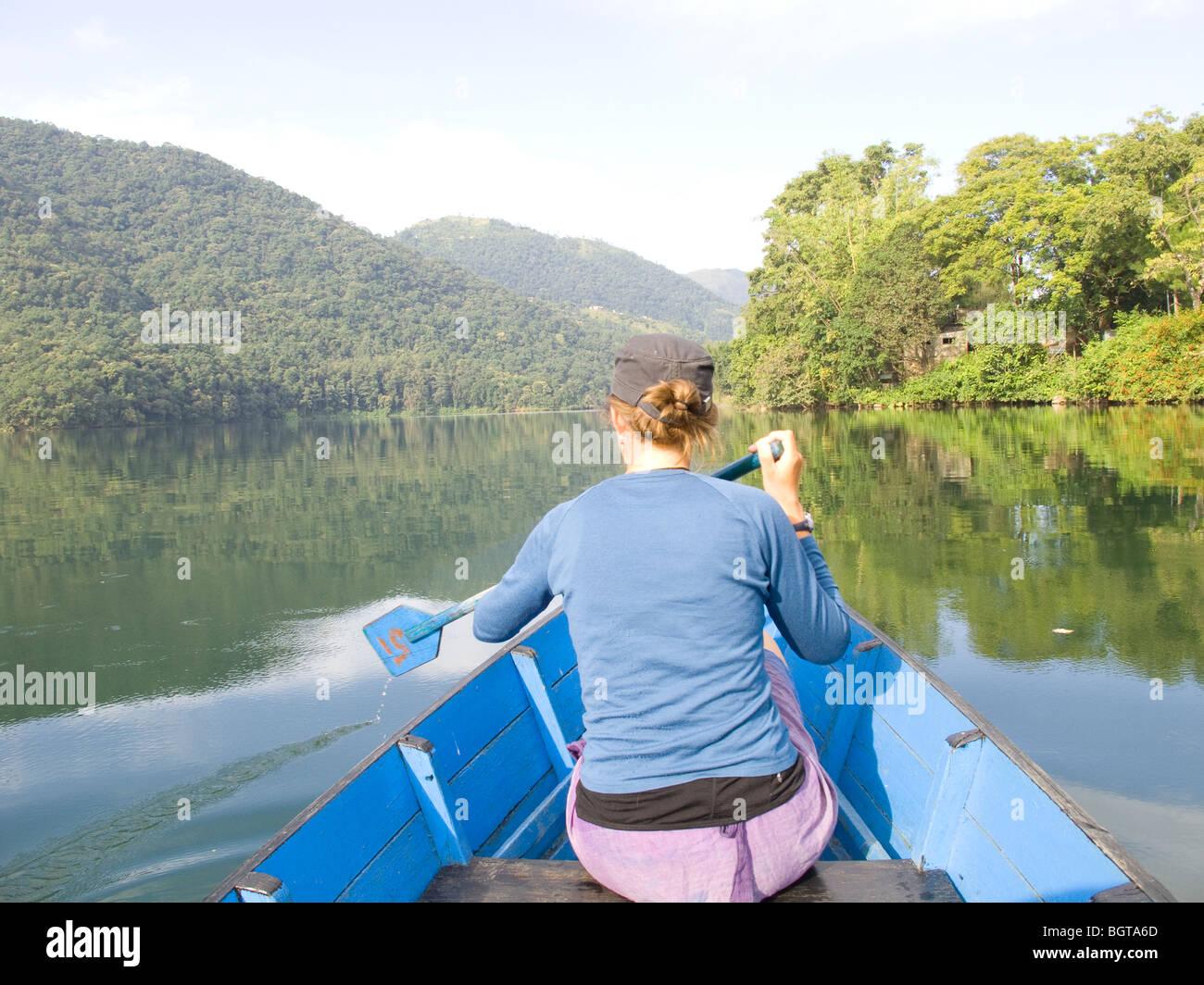 A woman rowing a canoe on Phewa lake, Pokhara, Nepal. - Stock Image