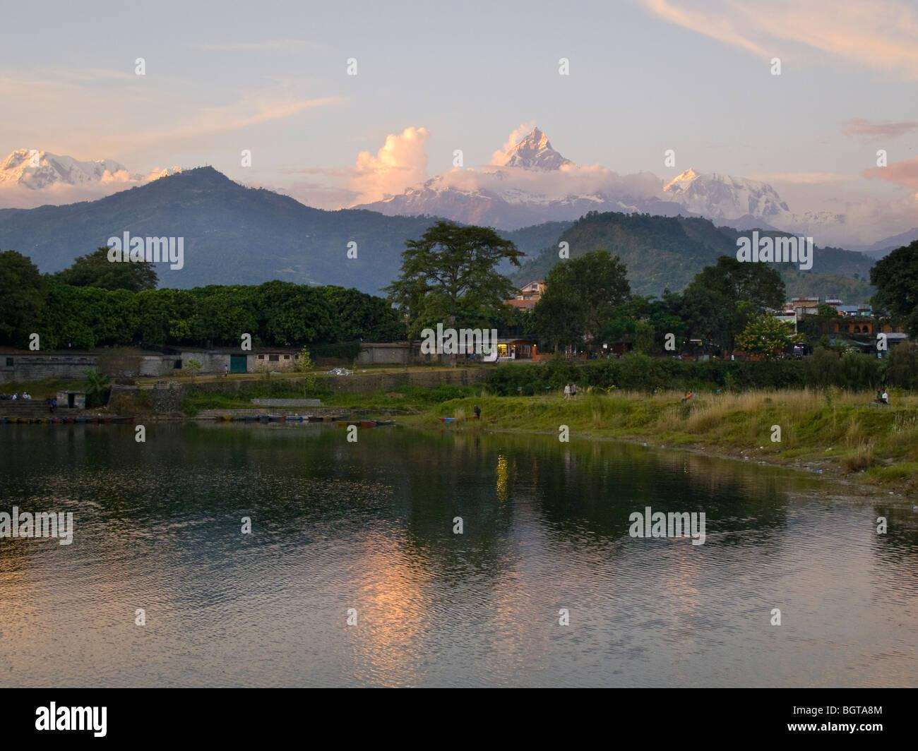 Machhapuchhare peak rising above Phewa lake and the town of Pokhara, Nepal. - Stock Image
