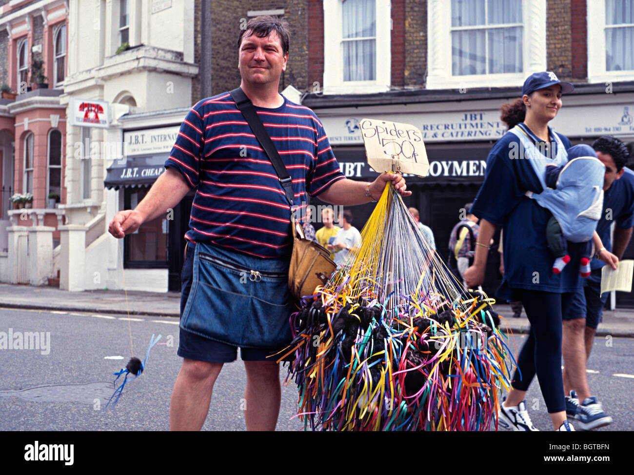 42623a2ab8 nottinghill carnival street parade in london with a man selling whistles -  Stock Image