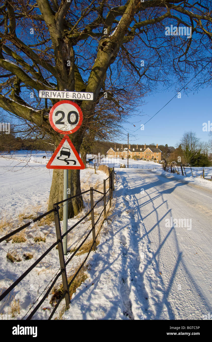 Warning signs, 20 m.p.h. and slippery road informing motorist of the hazard on the road leading to the village of - Stock Image