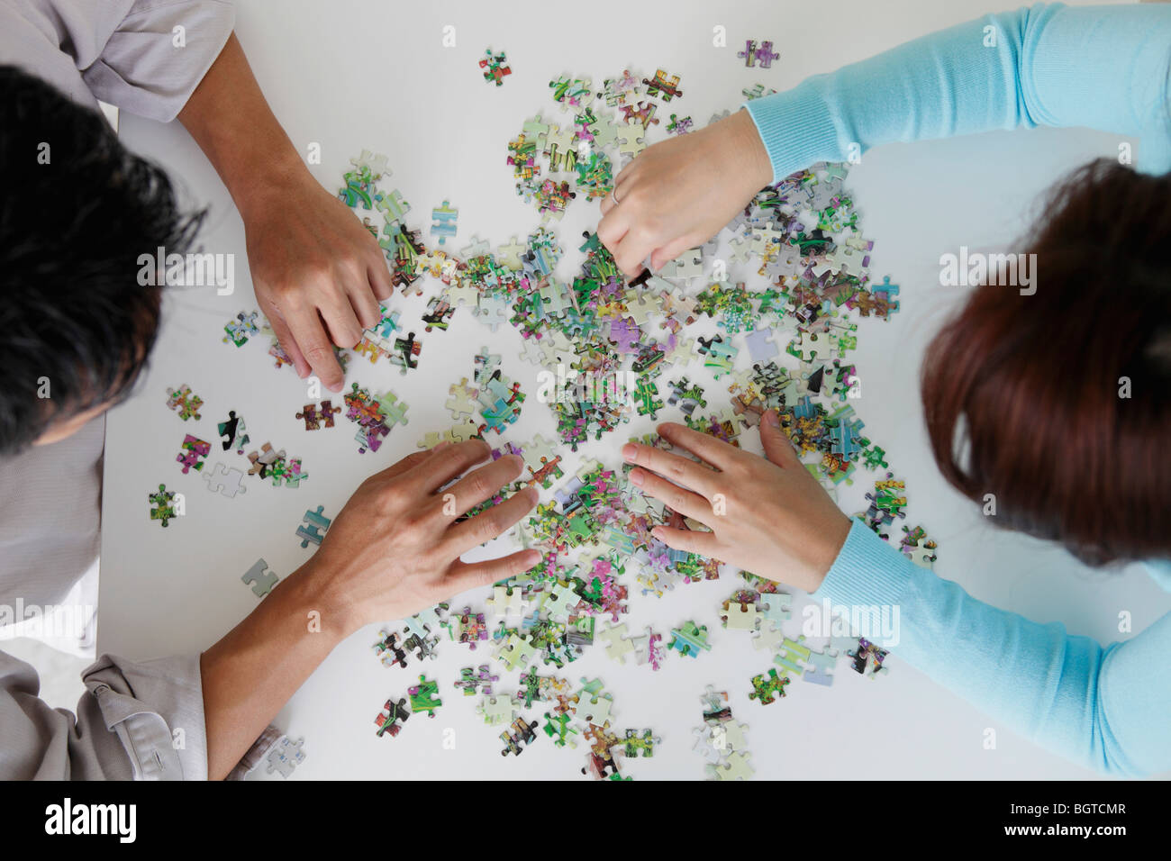 top view of couple putting puzzle together - Stock Image