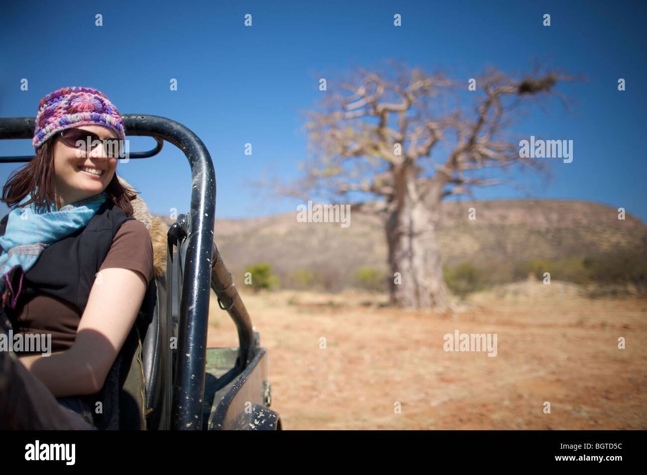 Young woman sitting in motor vehicle with Baobab tree in background, Kunene river area, Kaokoland, Namibia - Stock Image