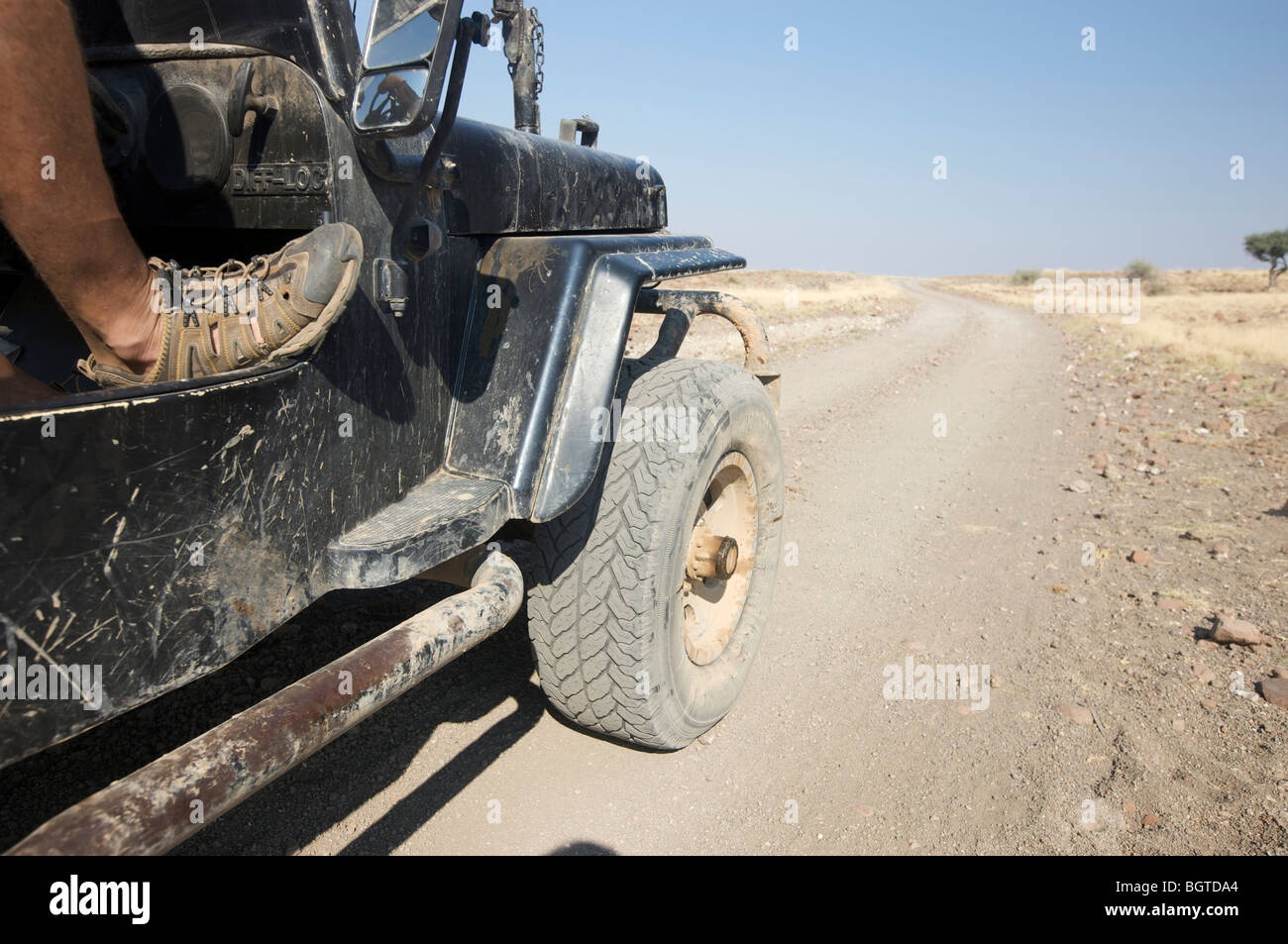 Low angle view of side of motor vehicle with drivers foot resting on the frame work, Marienflusstal area, Kaokoland, - Stock Image