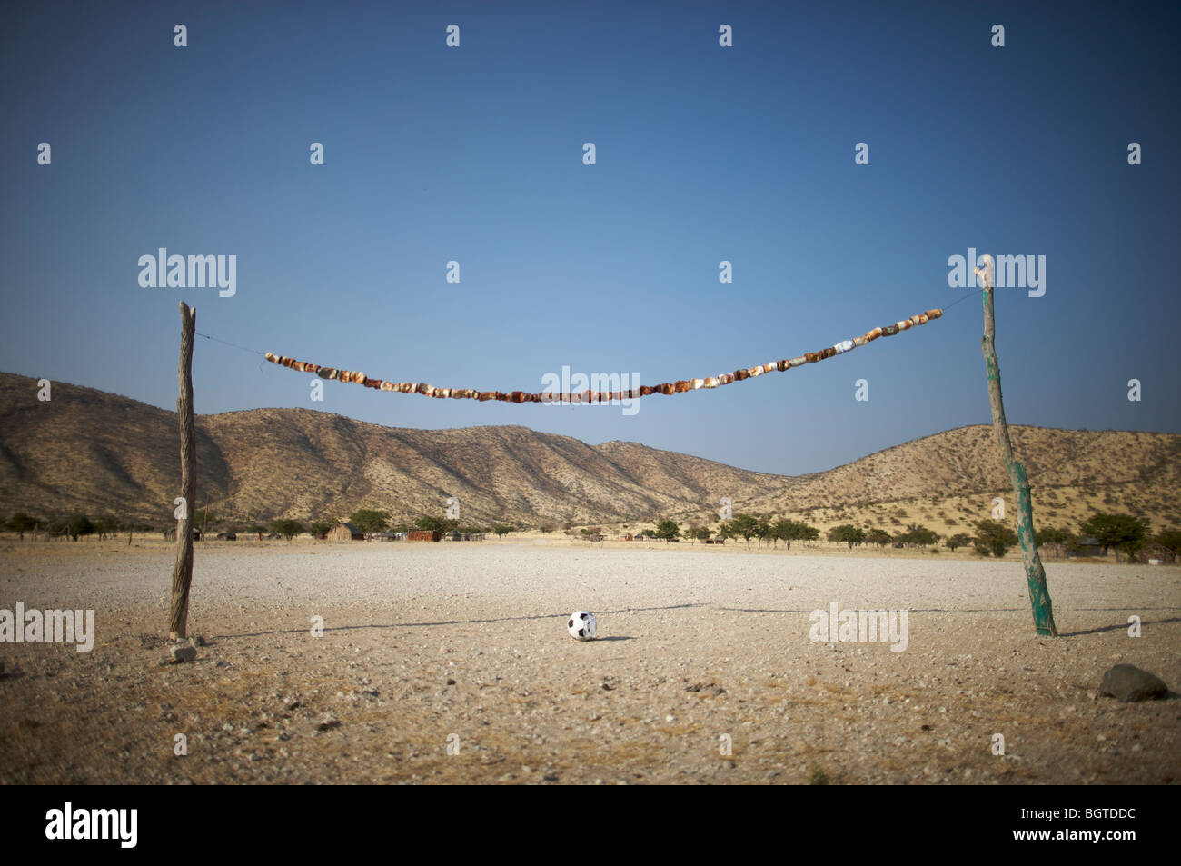 Rustic rural soccer field made of tree branches and cans, Epupa falls area, Kaokoland, Namibia - Stock Image