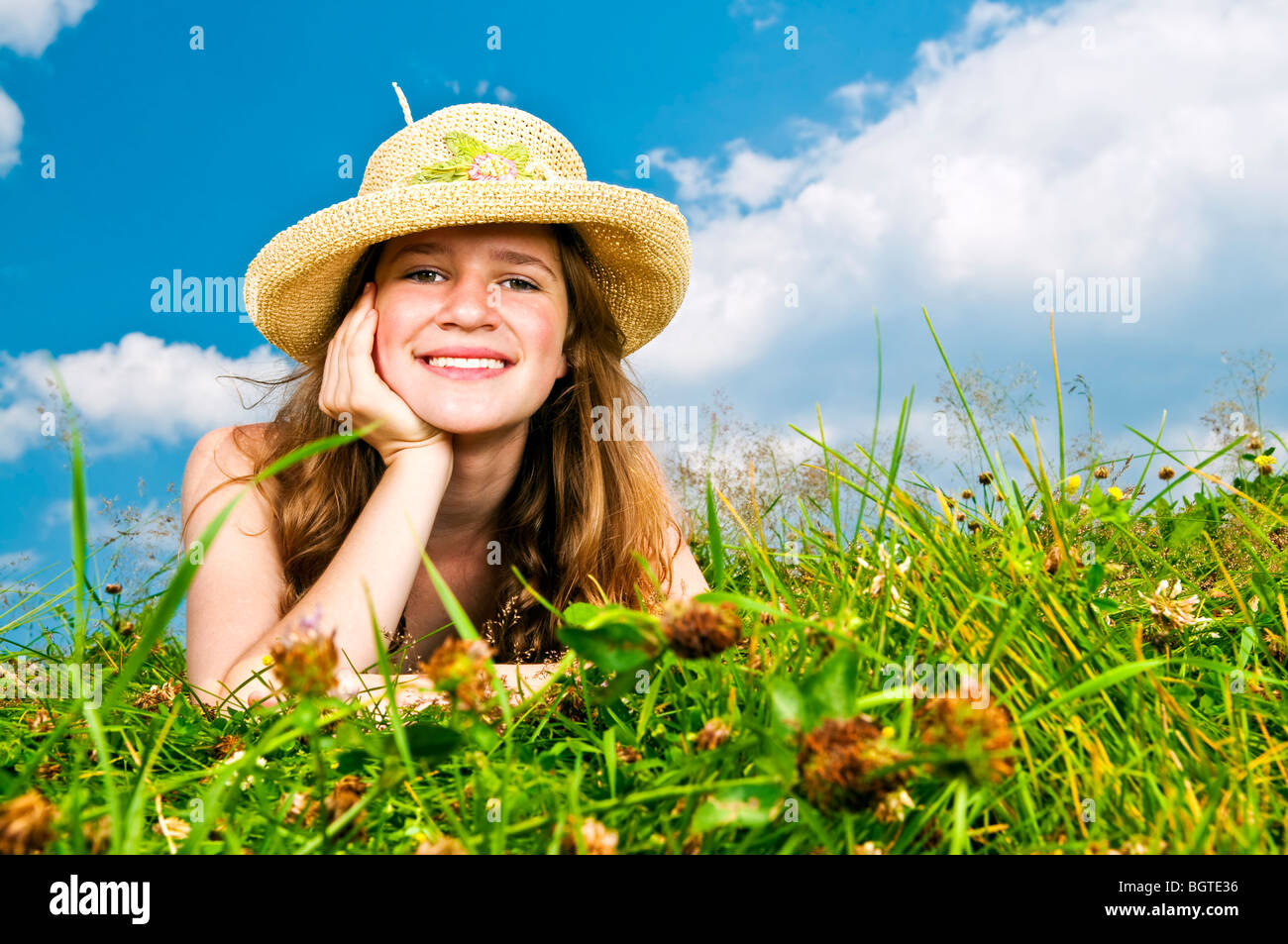 Young teenage girl laying in summer meadow resting chin on hand in straw hat Stock Photo