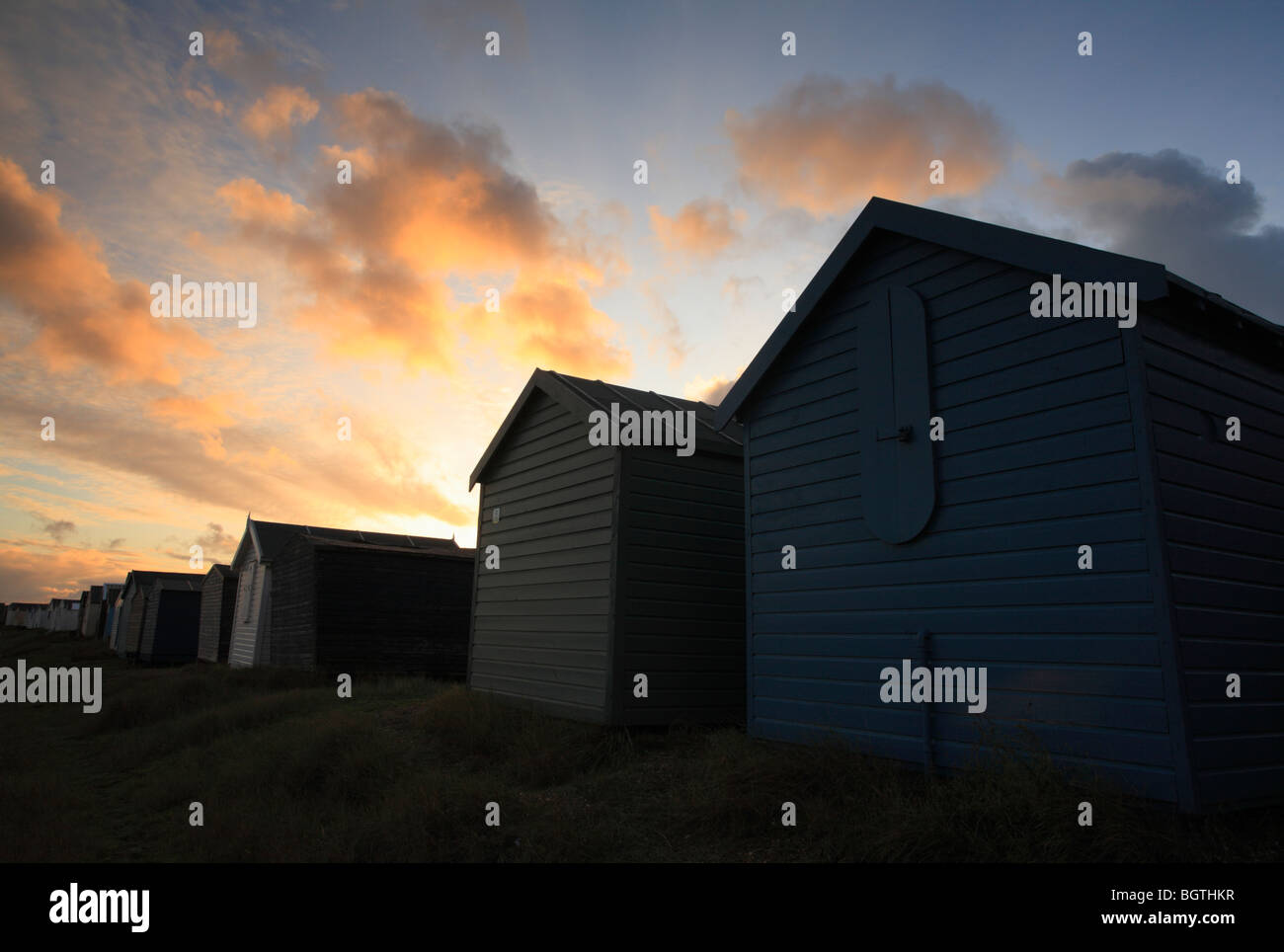 Beach huts at Heacham on the Norfolk coast against the sunset. - Stock Image