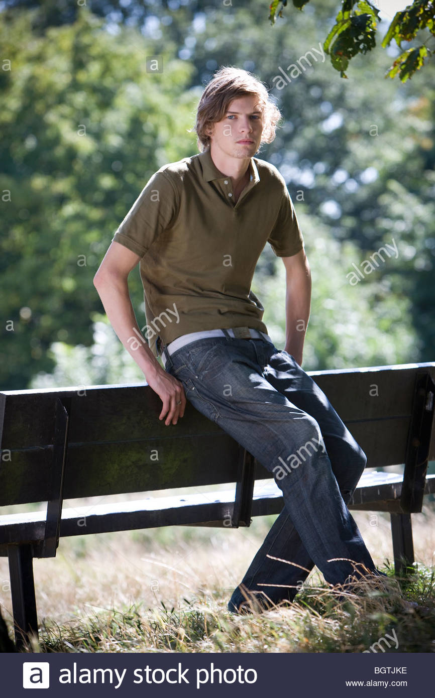 A young man leaning against a bench in a park - Stock Image