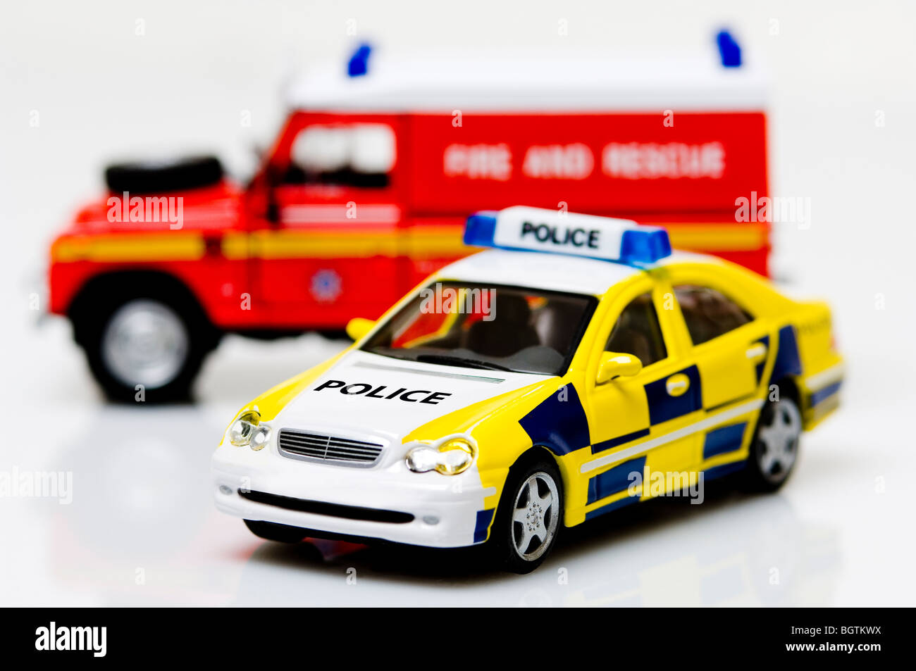 Toy British Police car with Fire and Rescue vehicle in the background Stock Photo