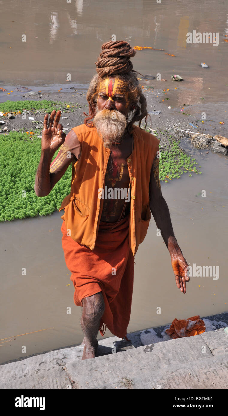 Full length shot of Sadhu washing by the river at Pashupatinath Temple, Kathmandu - Stock Image