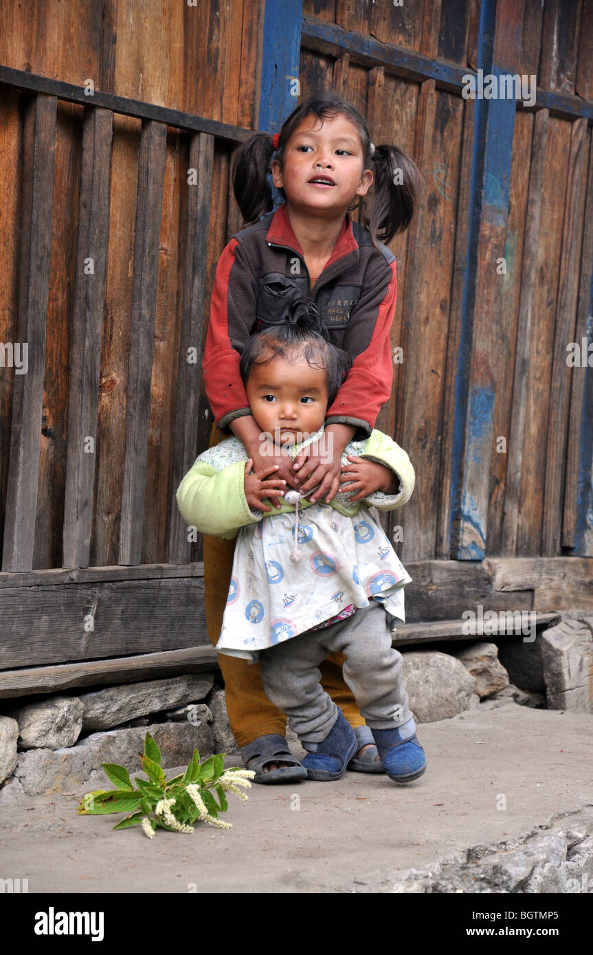 Young Nepalese girl, holding her younger sister, both staring out of photo - Stock Image