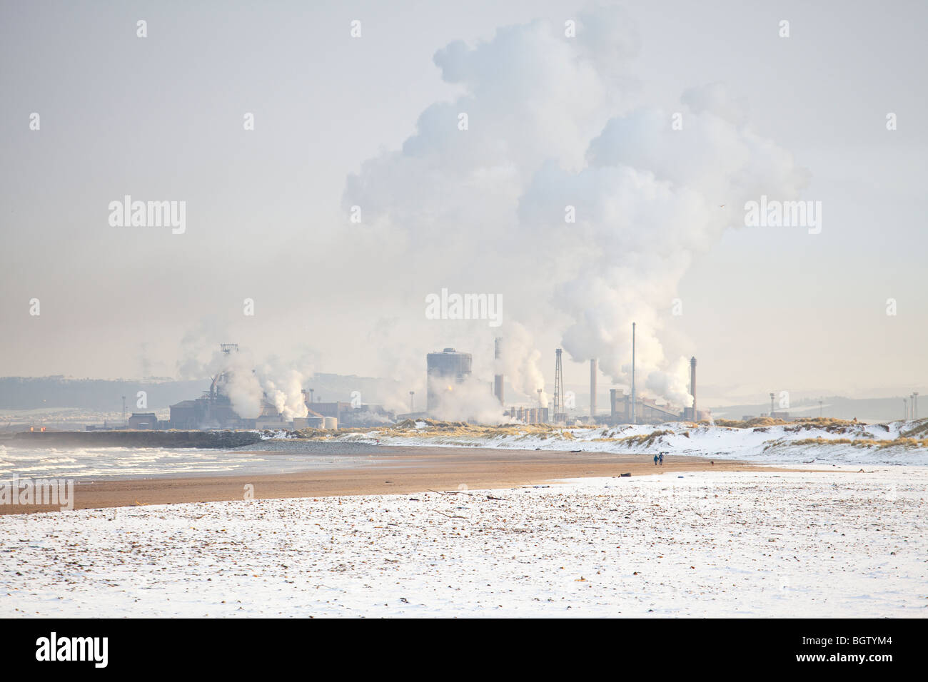 Seaton beach at low tide on a winter's day with the corus steelworks in the background - Stock Image
