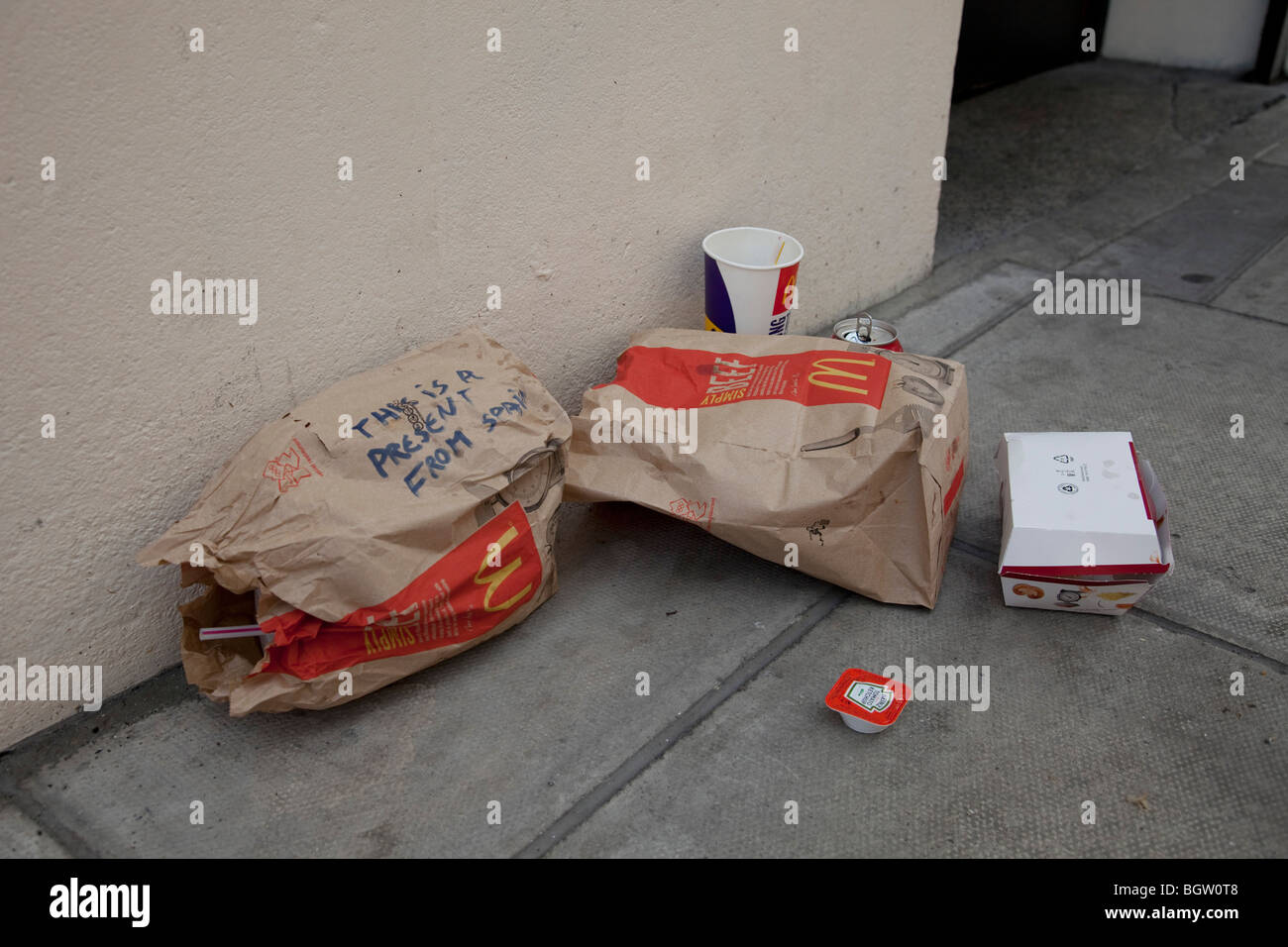 McDonalds litter. Someone has written 'This is a present from Spain' on the rubbish. - Stock Image