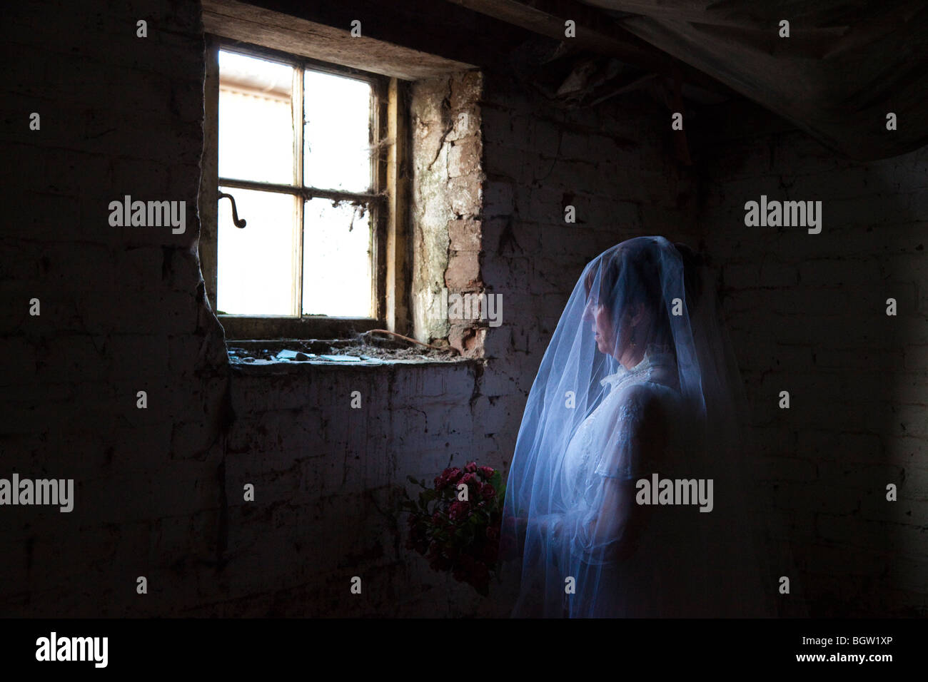 woman appearing like a ghost in old building - Stock Image
