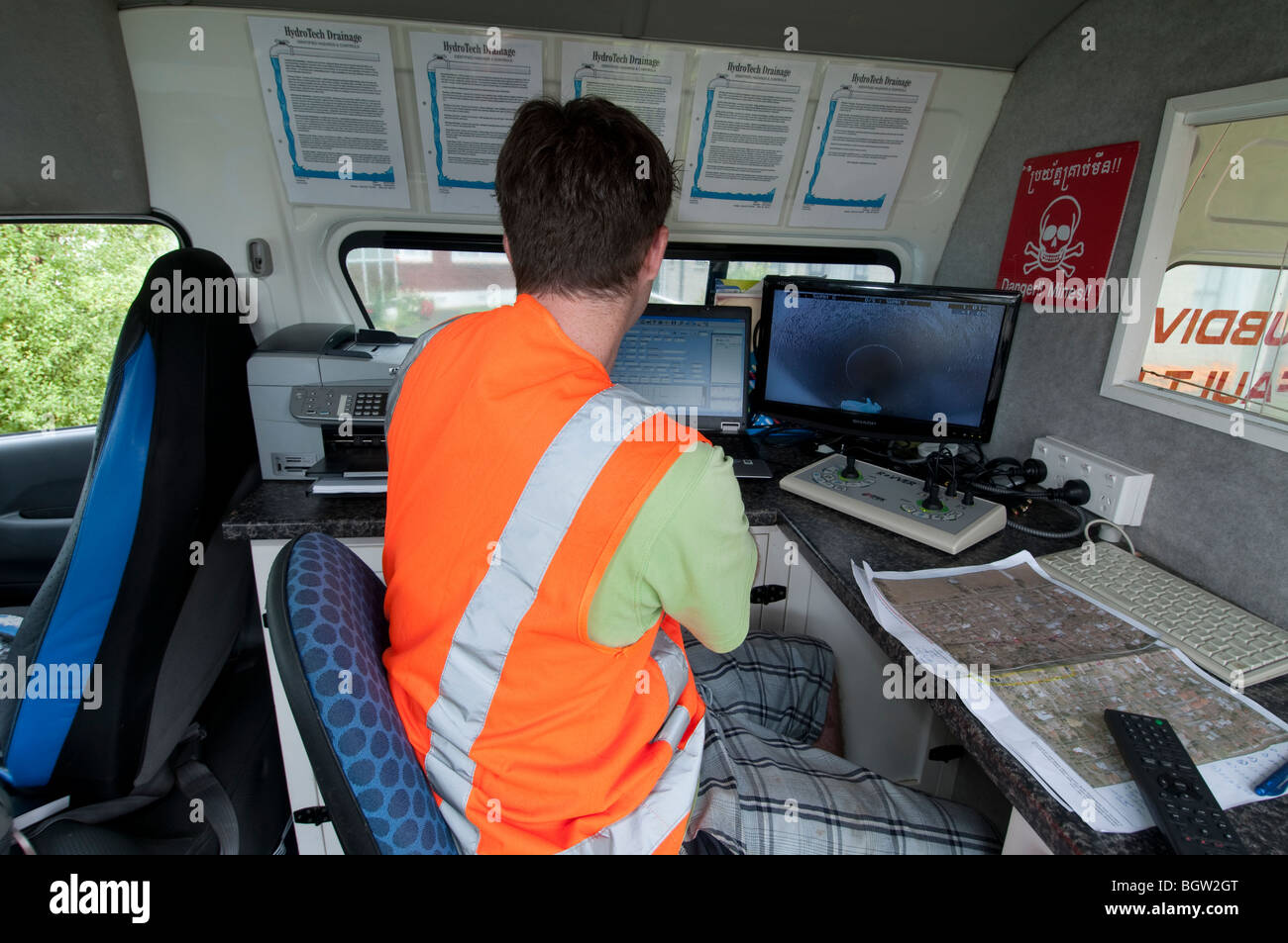 Young man inside van guiding remote video camera through underground pipes looking at live camera footage on screen - Stock Image