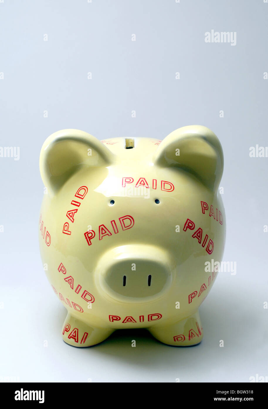 PIGGYBANK COVERED WITH 'PAID' STAMPS RE FINANCIAL DEBT,DEBTS,LOAN,LOANS,PAY,OFF,PAID. THE ECONOMY RECESSION - Stock Image