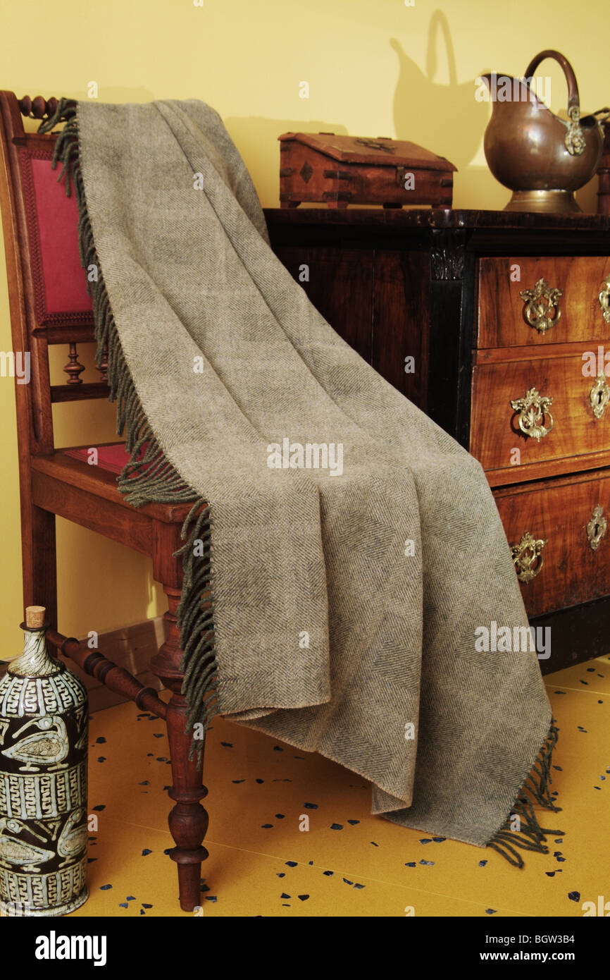 Ornamental antique furniture and a woven throw - Stock Image