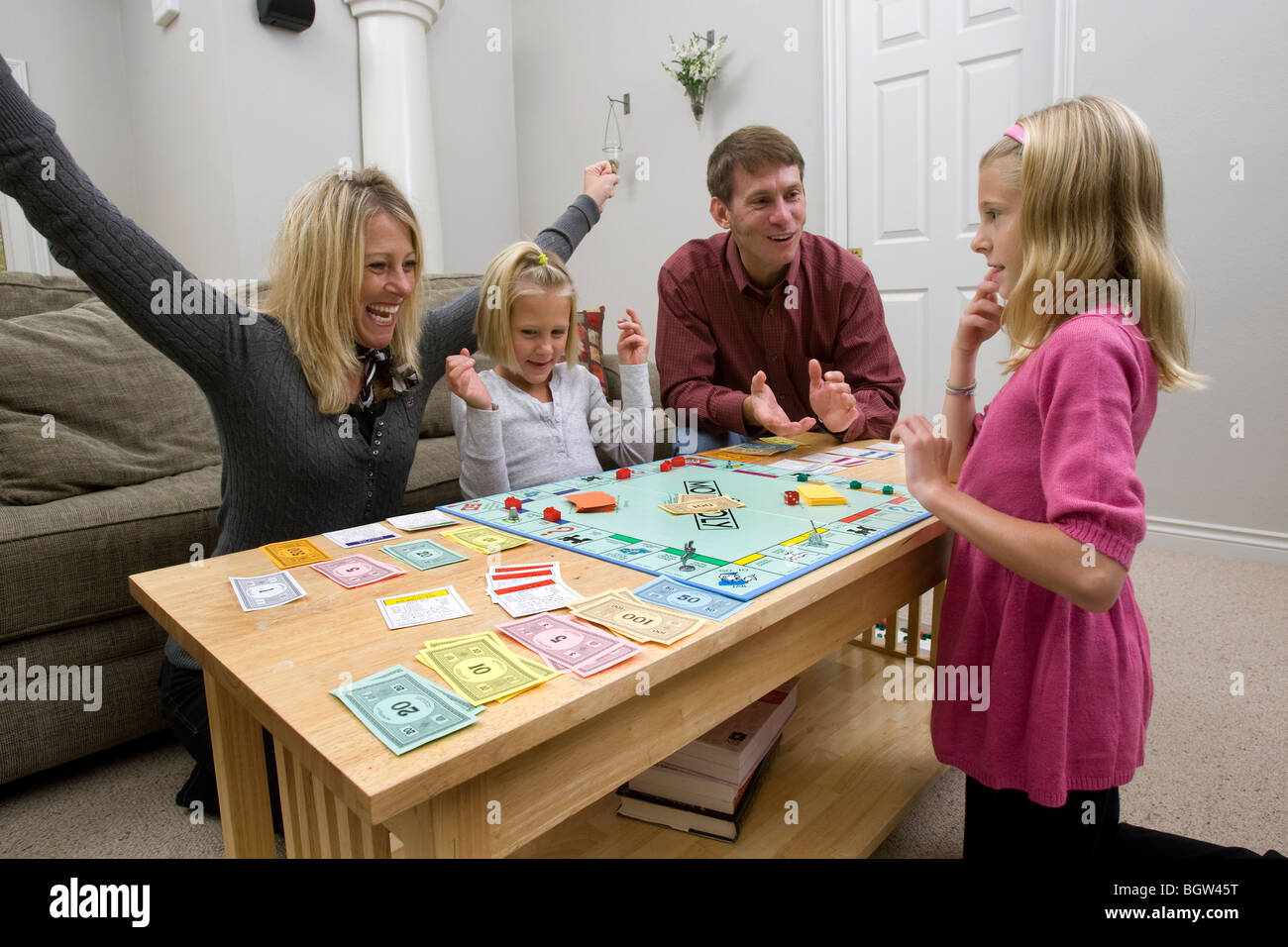 Family playing board game, Monopoly - Stock Image
