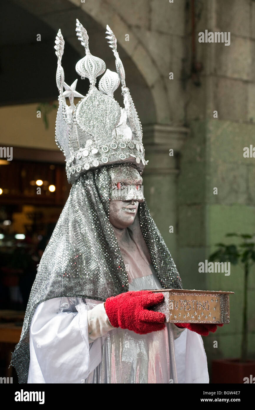 magical glittering silver costumed flame eyed king holding box of destinies performs in Sunday Zocalo Oaxaca City - Stock Image