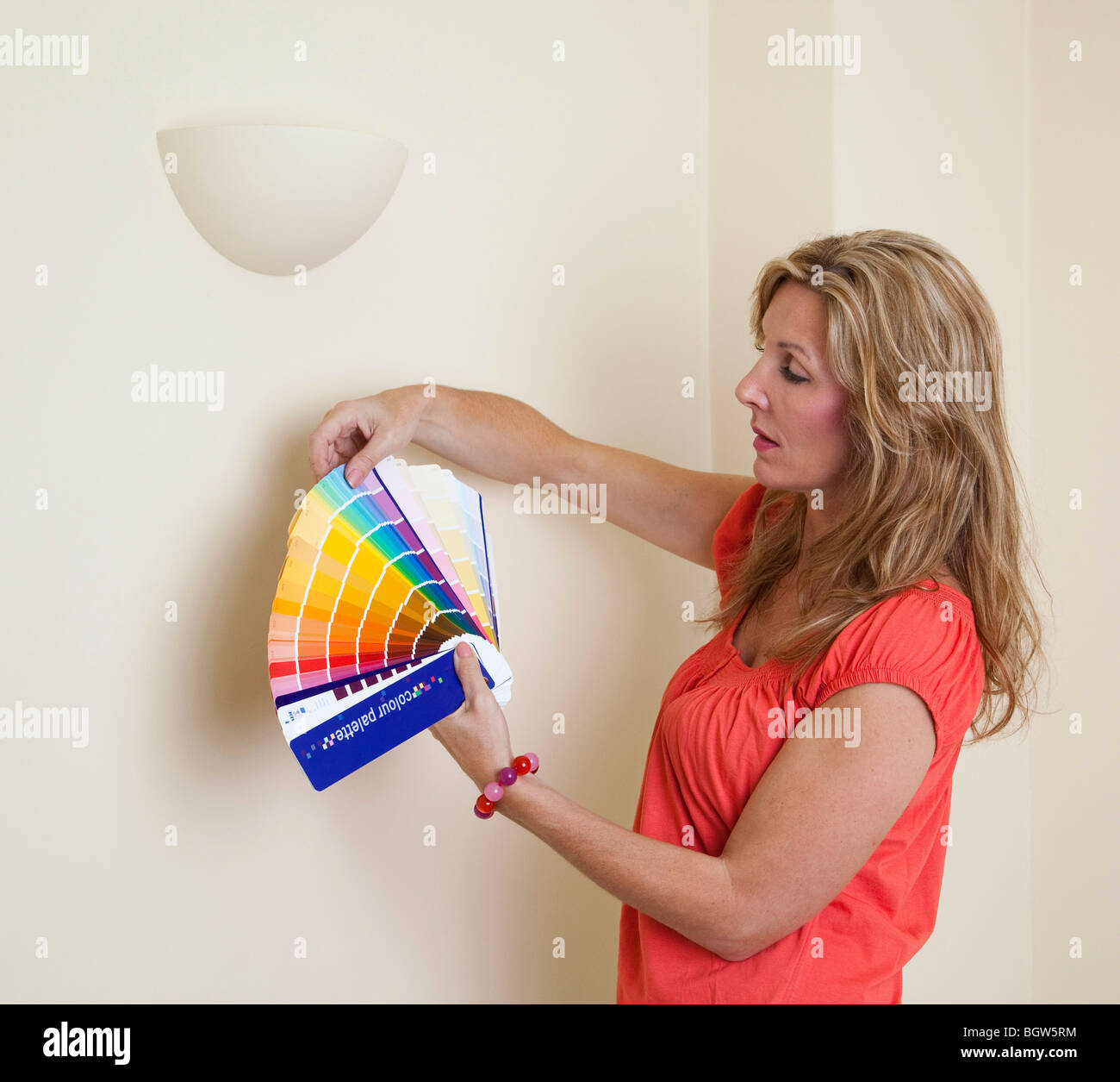 woman choosing colours for a wall from a paint sample book Stock ...