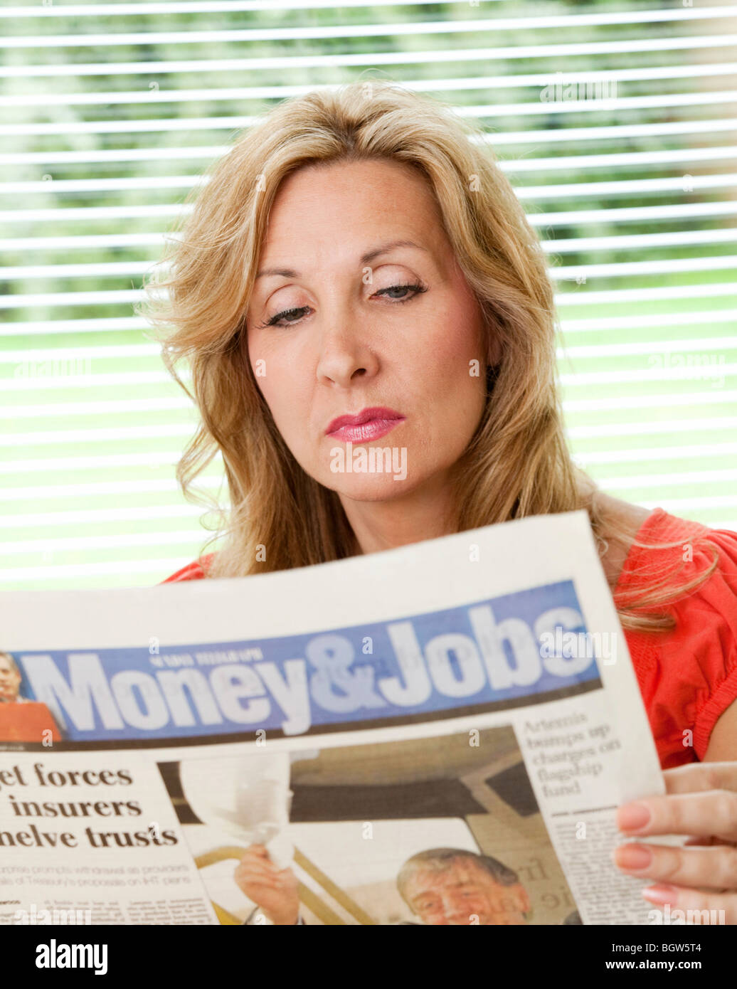 young woman reading a newspaper looking for a new job - Stock Image