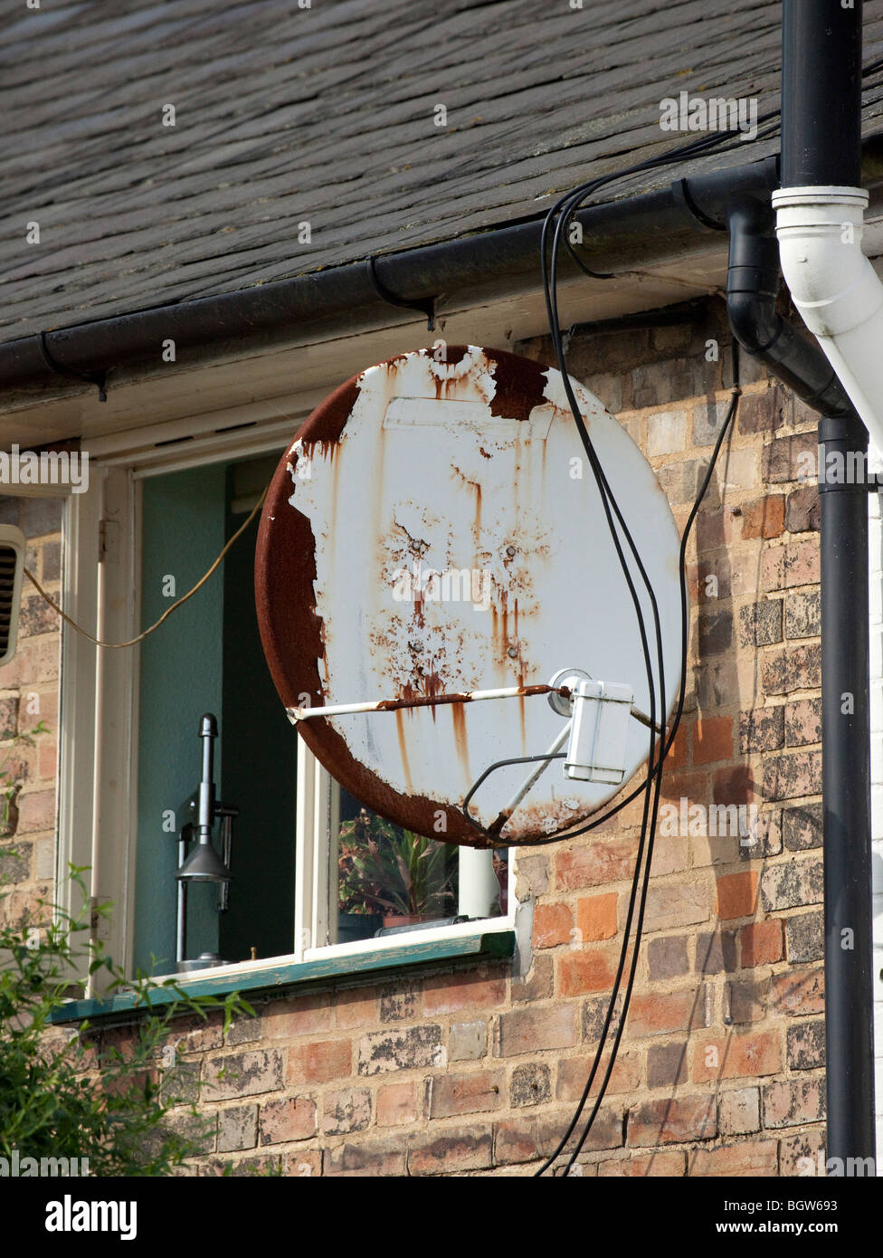 old rusty sky satellite dish on a house - Stock Image