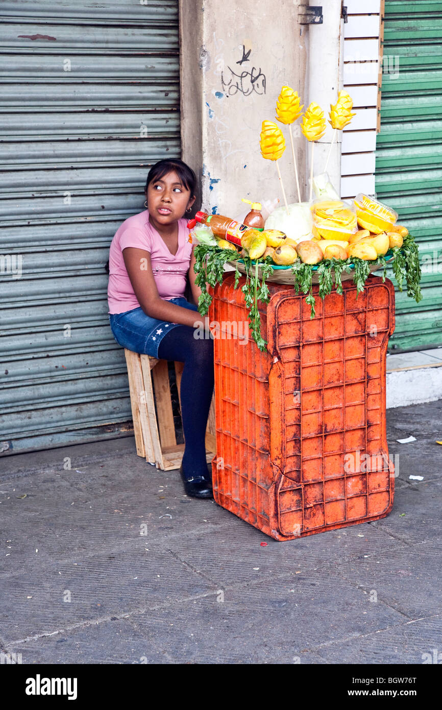 indigenous Mexican Indian tween in denim miniskirt sitting selling pineapple sculpted mangoes on sidewalk outside - Stock Image