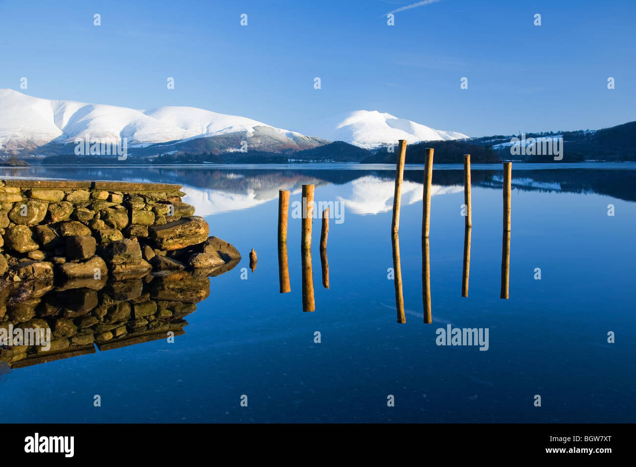 View over Derwentwater to snow clad Skiddaw and Blencathra or Saddleback and remains of old Jetty or Pier Lake District - Stock Image