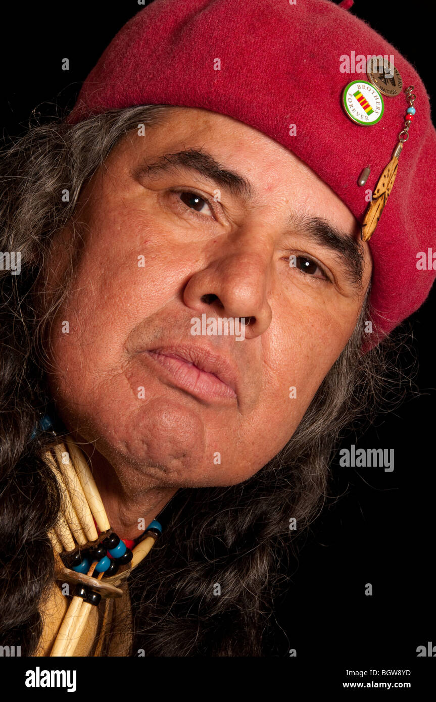Close up of native american indian Anishinabe  male in red hat, natural medicine man healer on black background - Stock Image