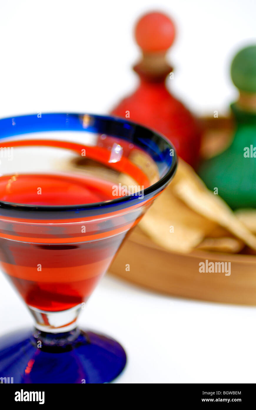 Colorful glassware holds a margarita, and sits near a tray containing nacho chips and more glassware. - Stock Image