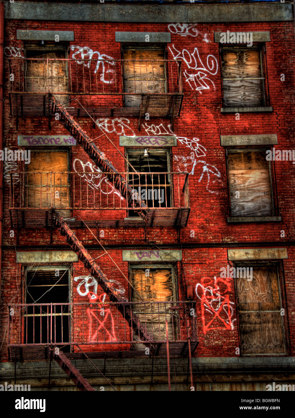 A boarded up brick buildingi, covered in graffiti.  Fire escape stairwells make a pattern between floors. - Stock Image