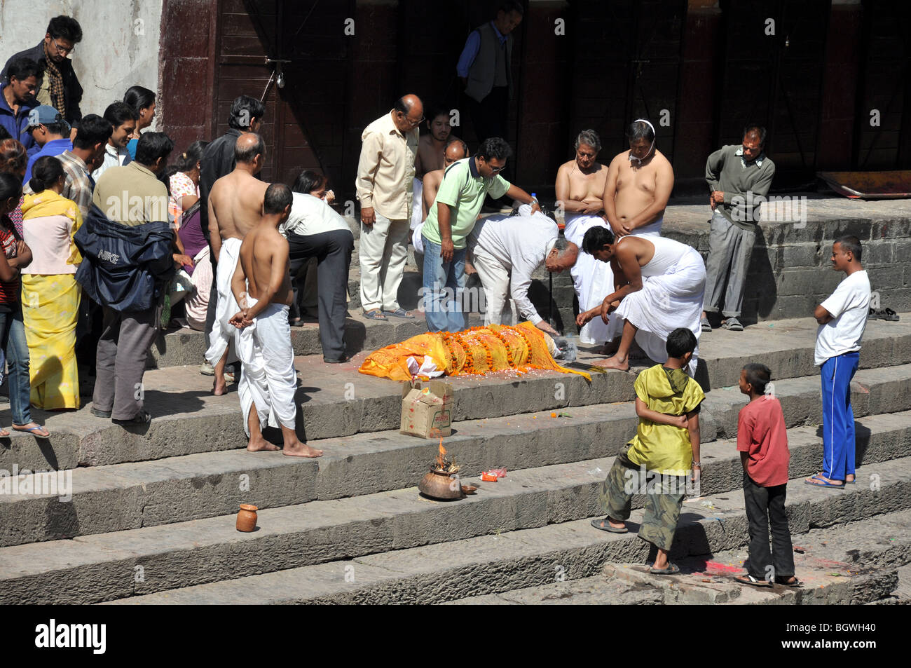 Ceremonial preparations for a cremation on the banks of the Bagmati river, in front of the Pasupatinath Temple - Stock Image