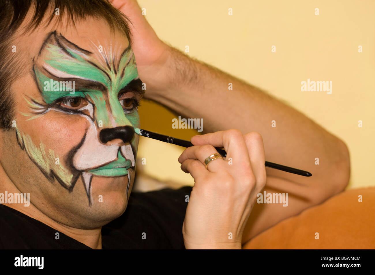 Makeup artist painting the man face. - Stock Image