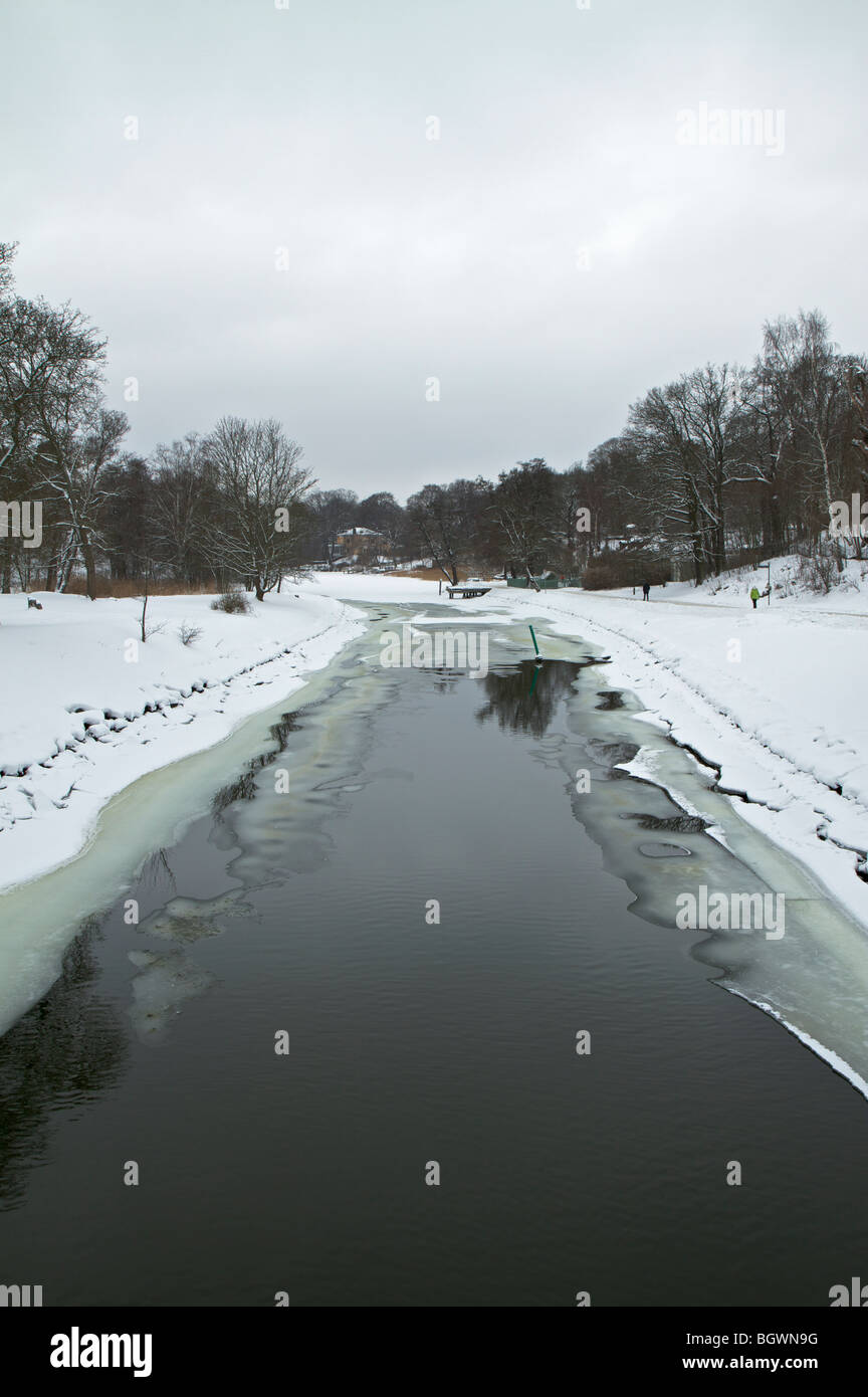 View looking down at partially frozen water way - Stock Image