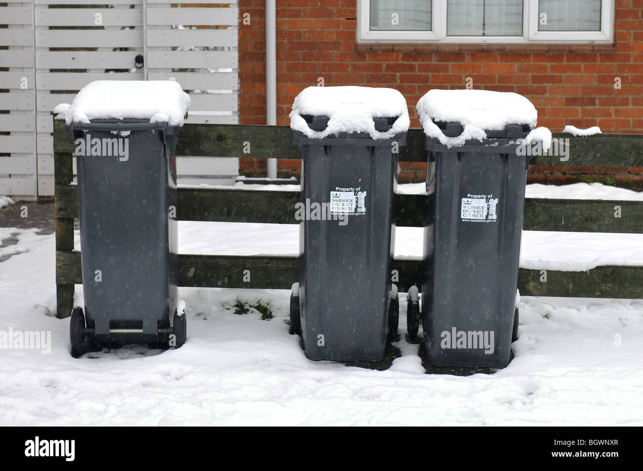 Domestic non-recyclable material bins put out for emptying in snowy weather, UK Stock Photo