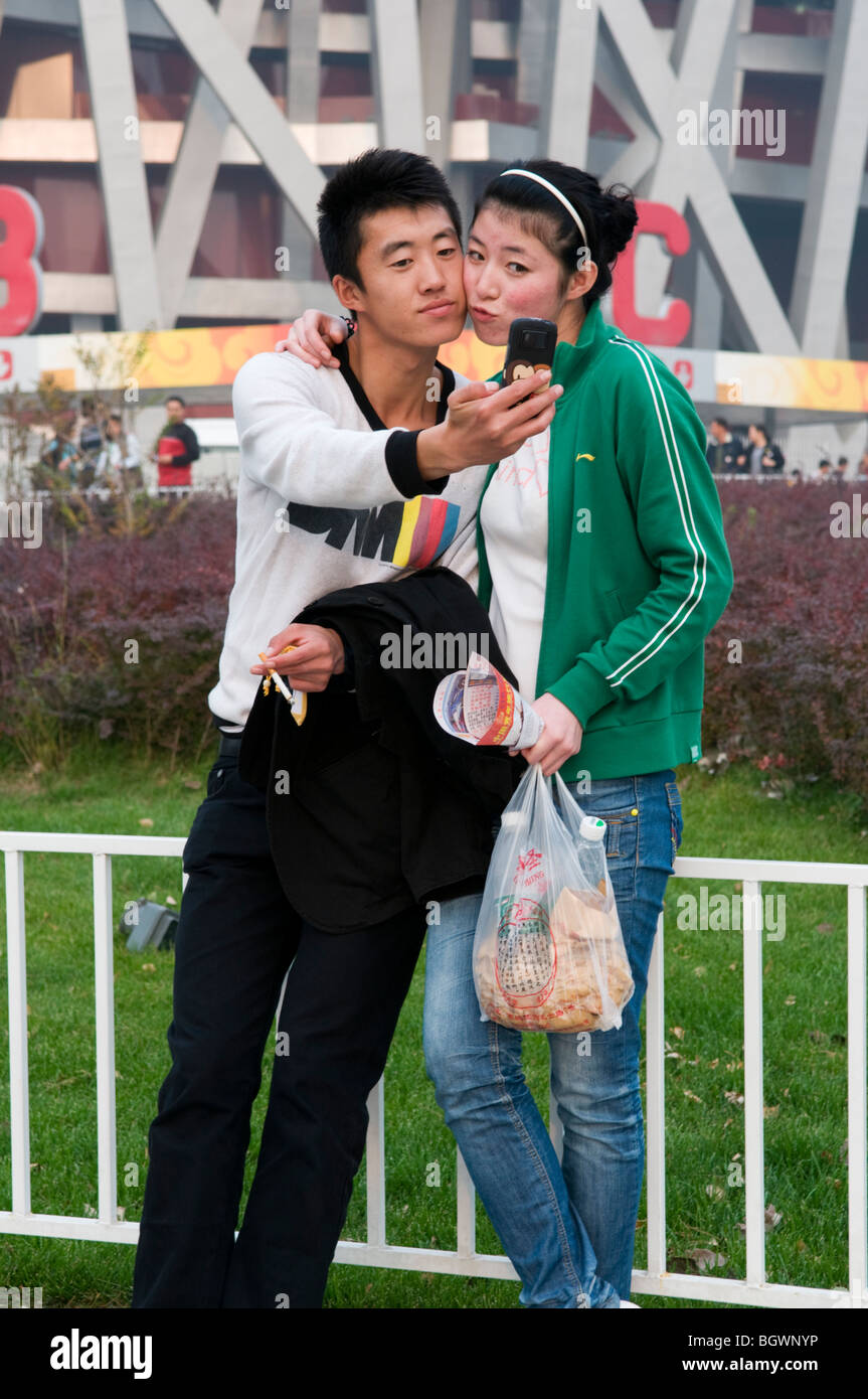 A young couple takes a selfie photograph with their mobile phone in front of the Beijing Olympic Stadium - Stock Image
