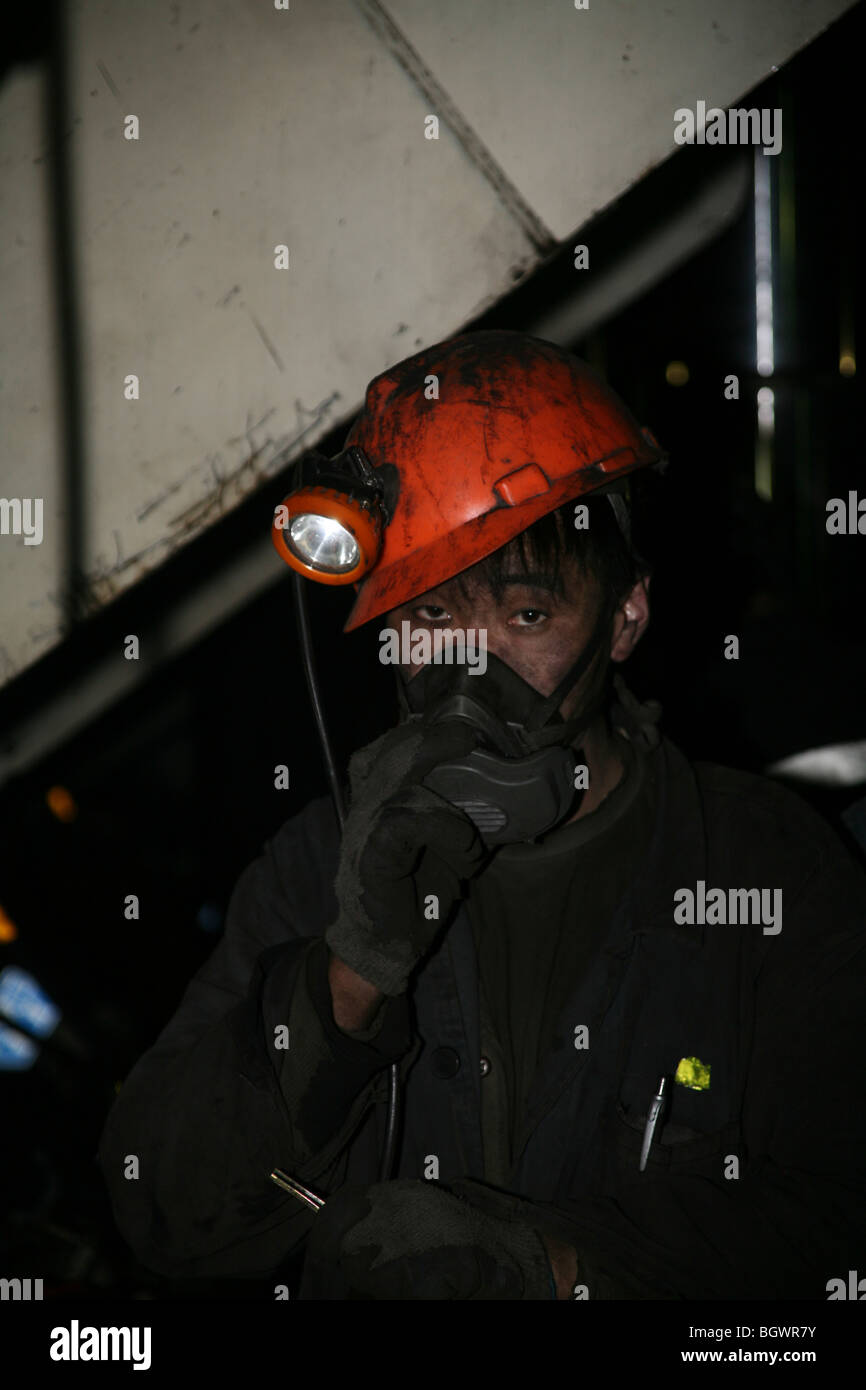 Sad looking Chinese coal miner with breathing apparatus - Stock Image