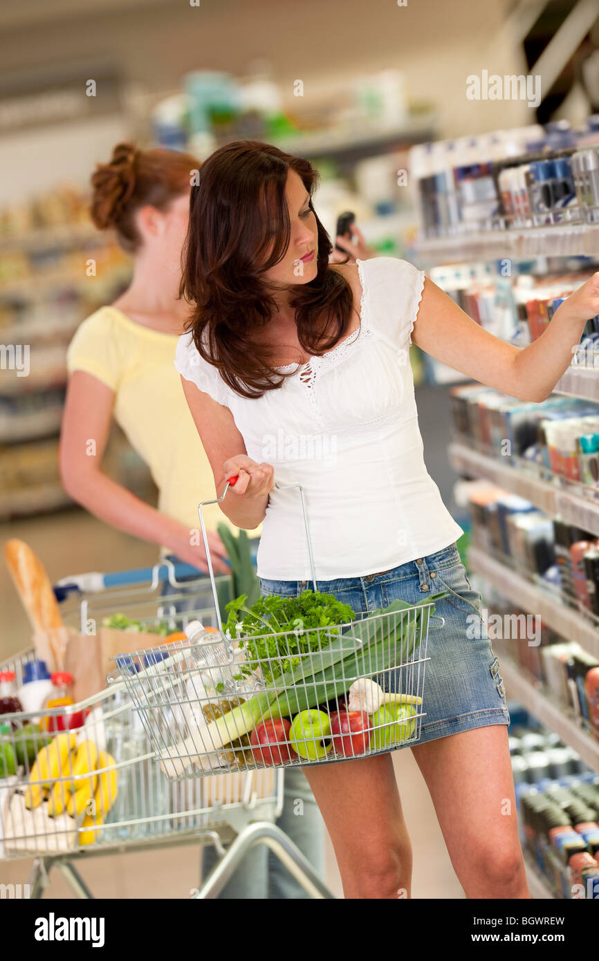 Shopping - Beautiful brunette in a supermarket and holding shopping basket - Stock Image