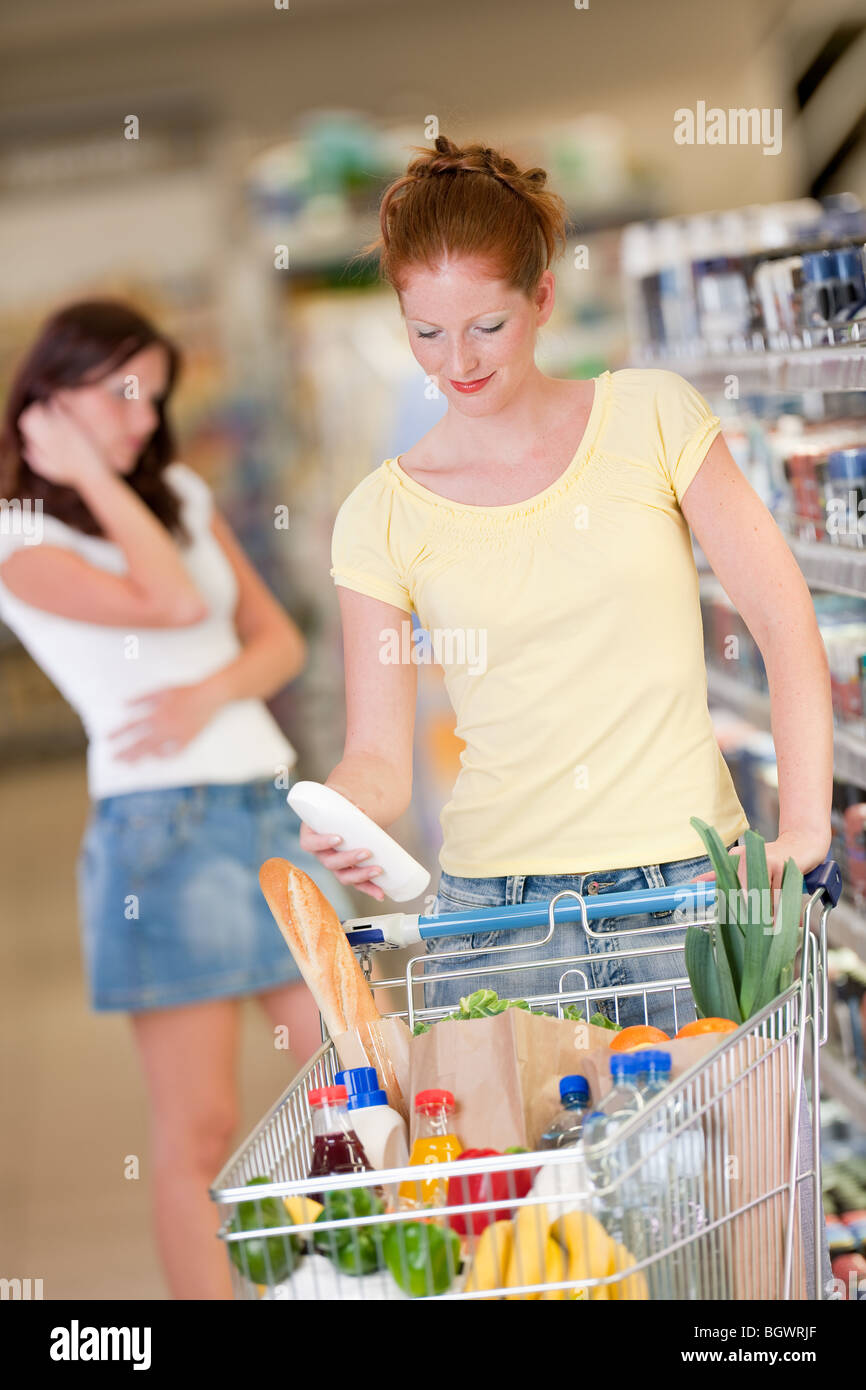 Shopping - Red hair woman holding bottle of shampoo in a supermarket - Stock Image