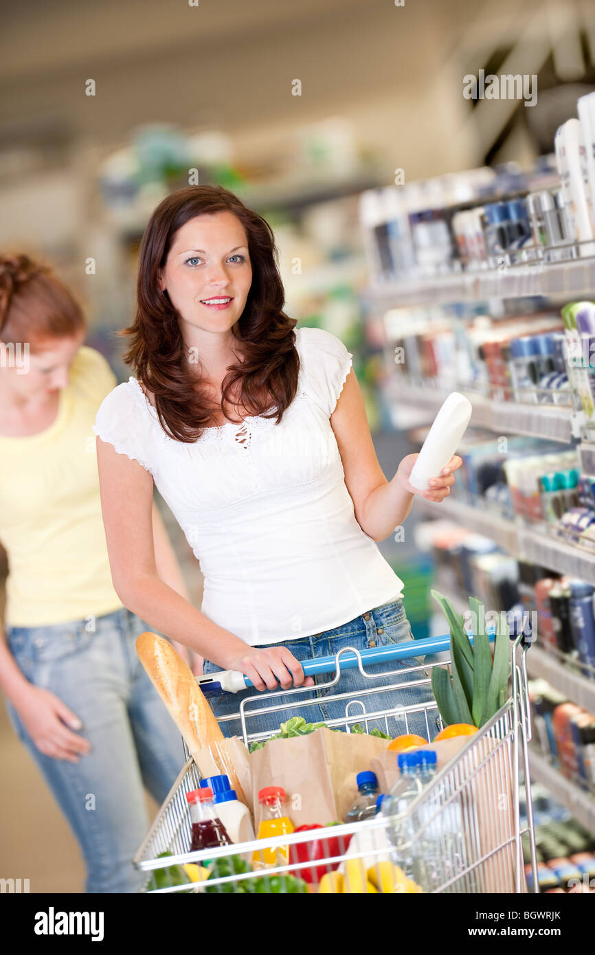 Shopping - Brown hair woman with cart holding shampoo - Stock Image