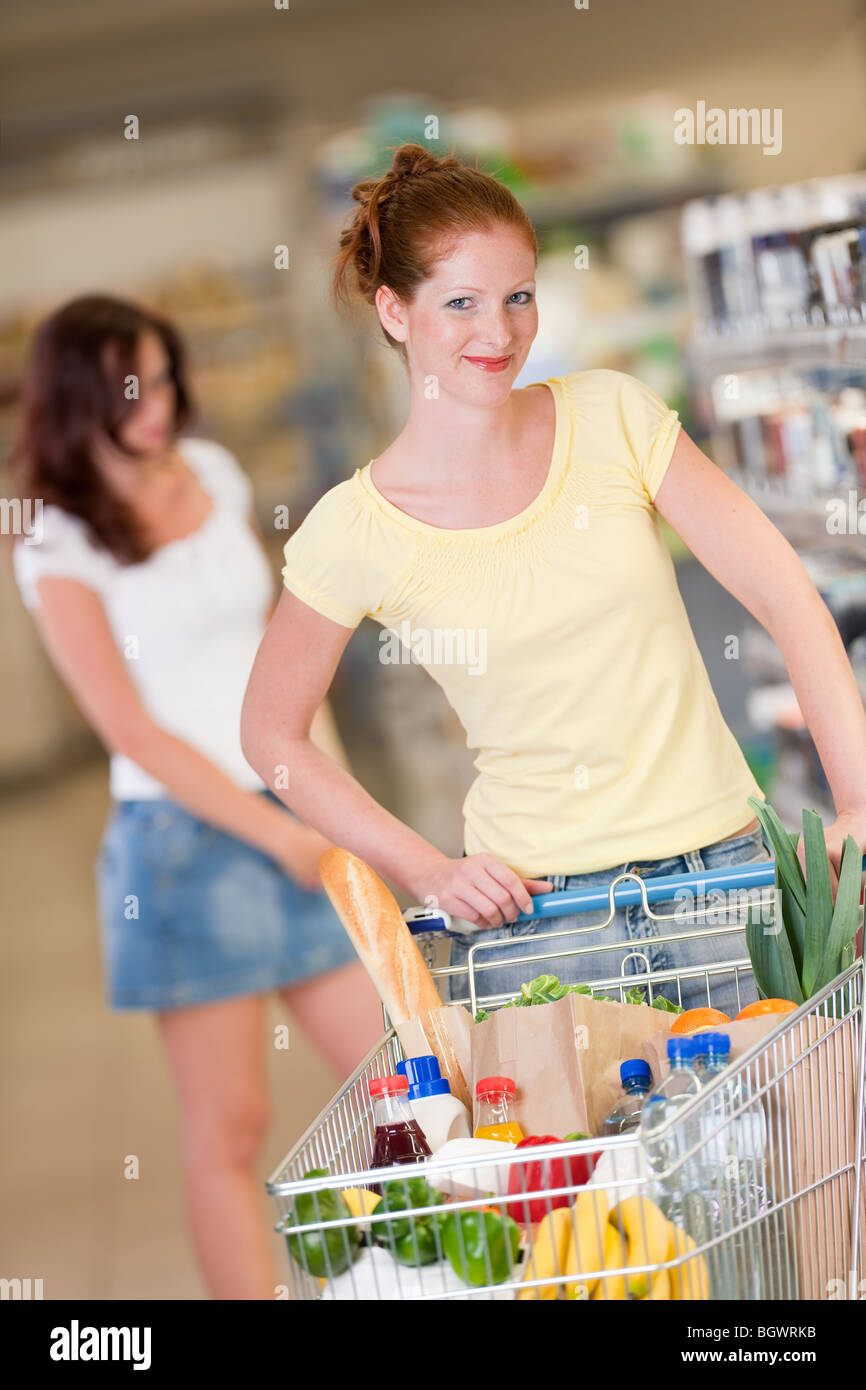 Shopping - Red hair woman with cart in a shopping mall - Stock Image