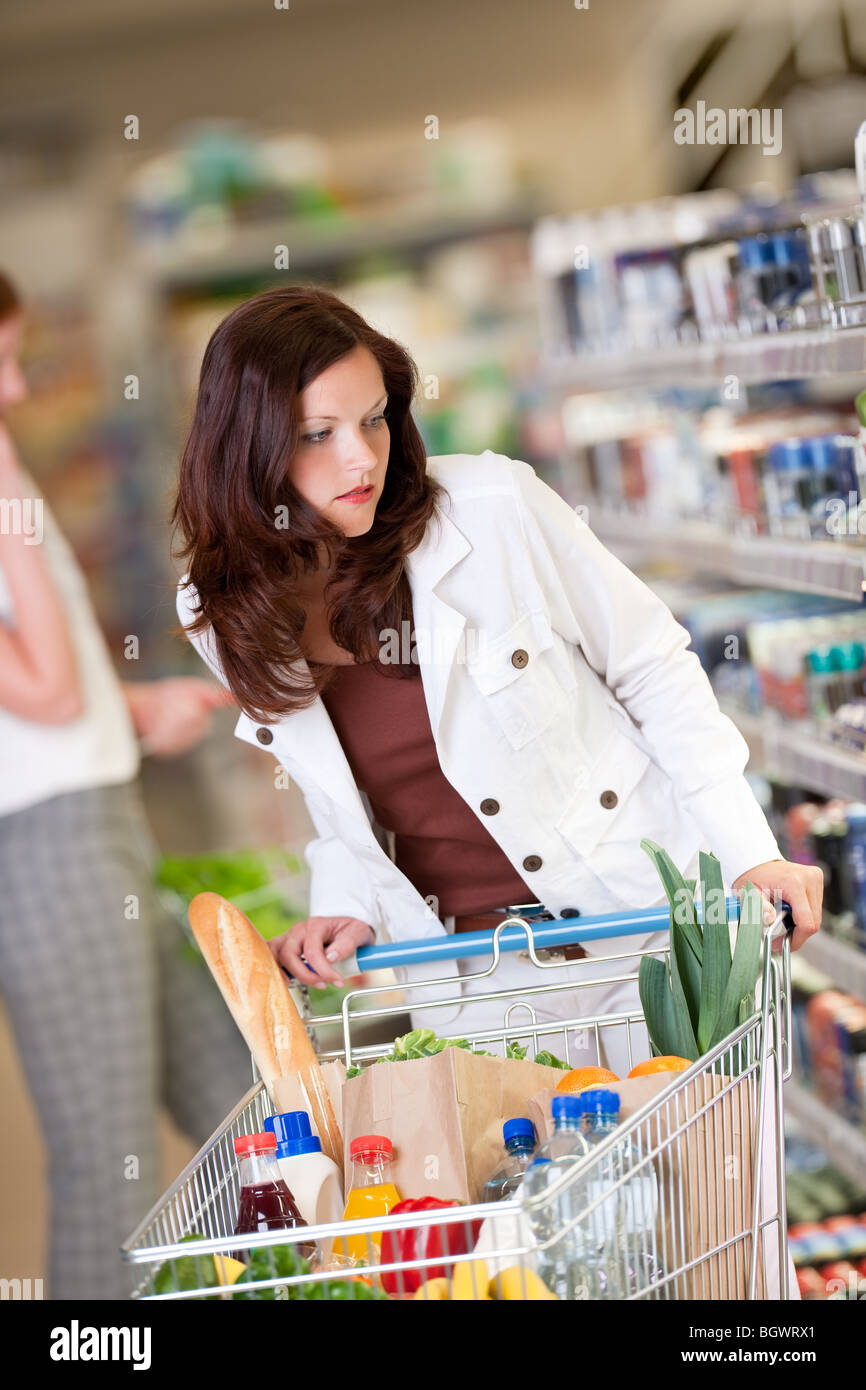 Shopping - Brown hair woman with a shopping cart in a supermarket - Stock Image